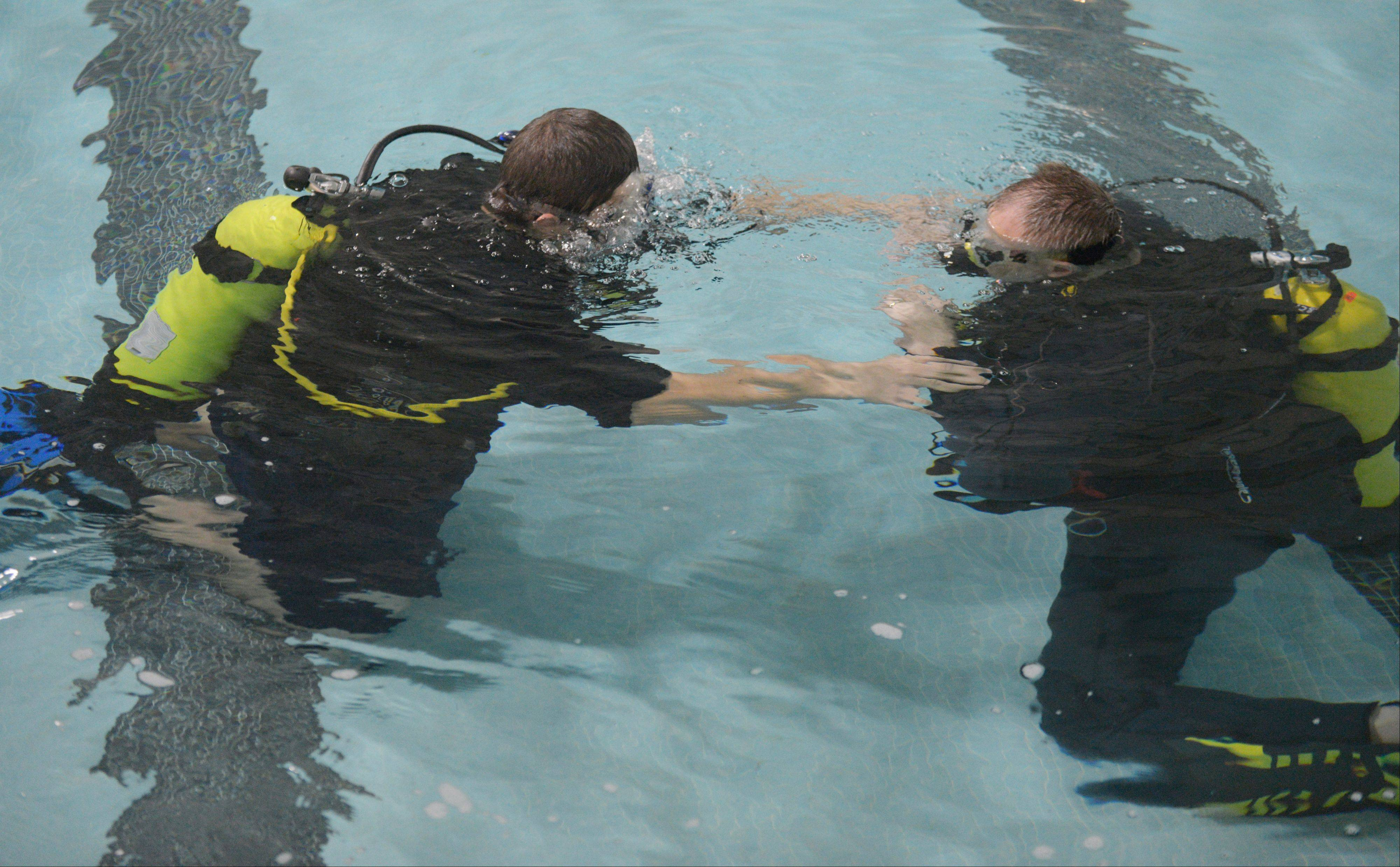 Pete Livorsi of Buffalo Grove, right, helps Neikos Fultz of Aurora begin to learn scuba diving Saturday in the East Aurora High School pool. Triple Threat Mentoring and S.T.A.R.S. International offered scuba lessons to about 15 urban teens who otherwise may never experience such an expensive hobby.