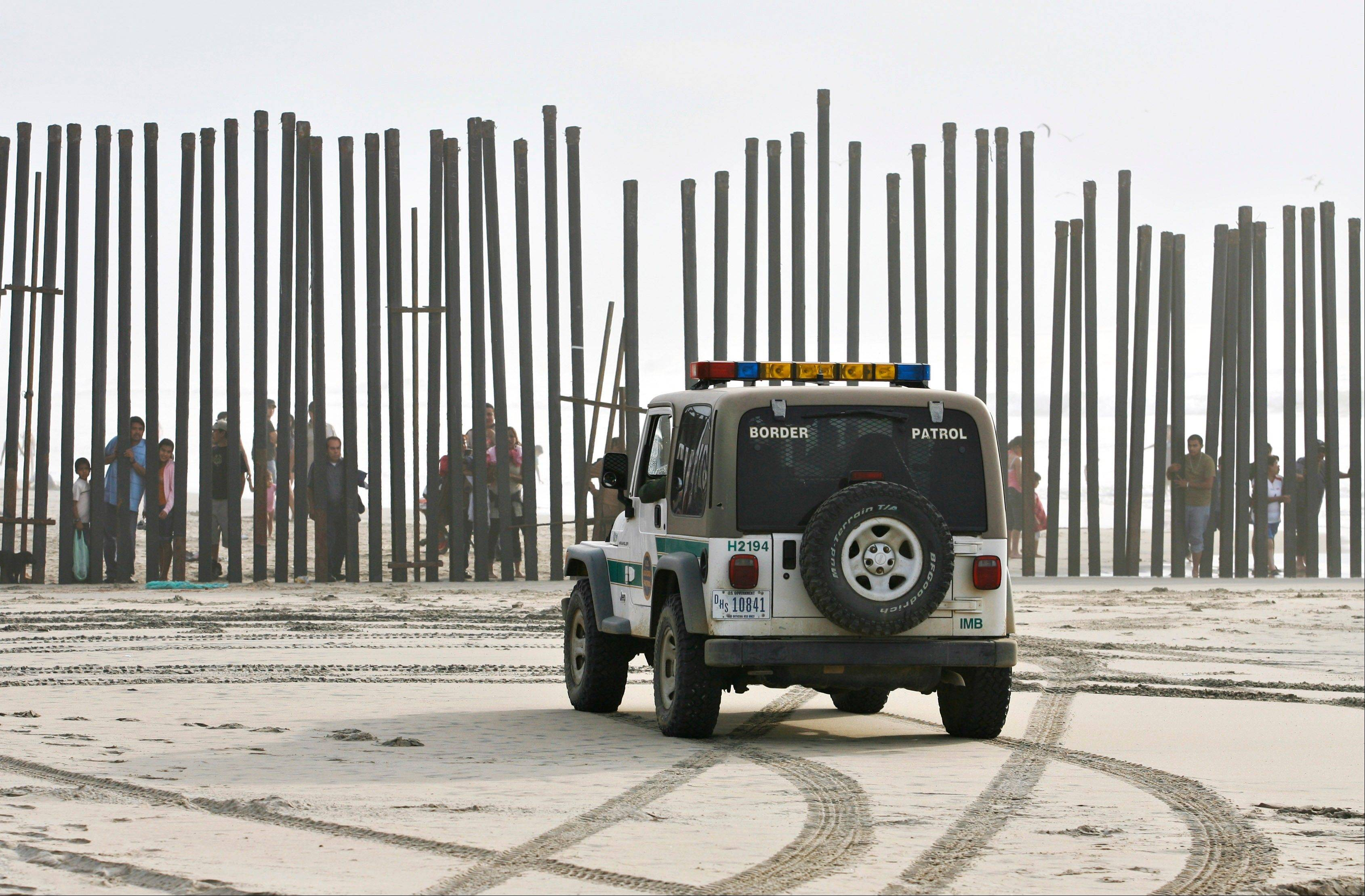 Associated Press/Jan. 18, 2009 A U.S. Border Patrol vehicle sits parked in front of a crowd of people peering through the U.S.-Mexico border fence at Border Field State Park in San Diego.