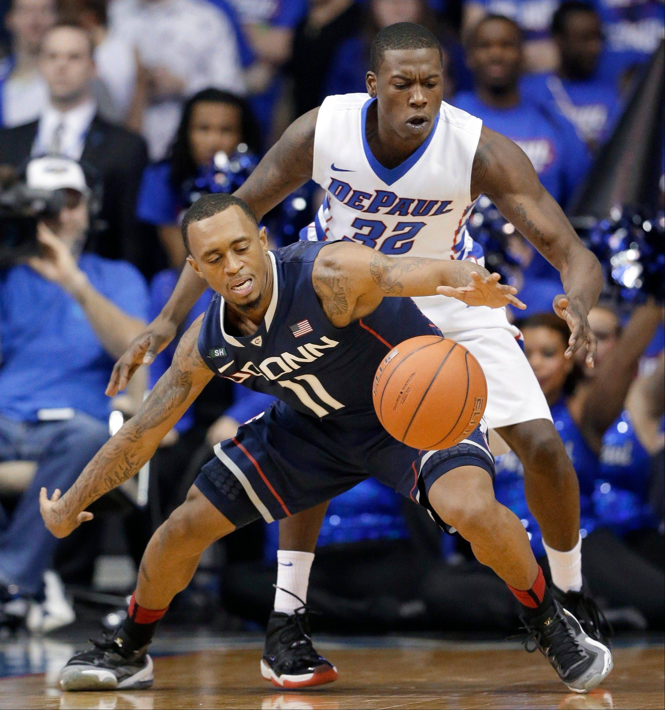 Connecticut guard Ryan Boatright (11) � who is from Aurora � controls the ball against DePaul guard Charles McKinney (32) during the game Saturday night in Rosemont. Connecticut won 81-69.