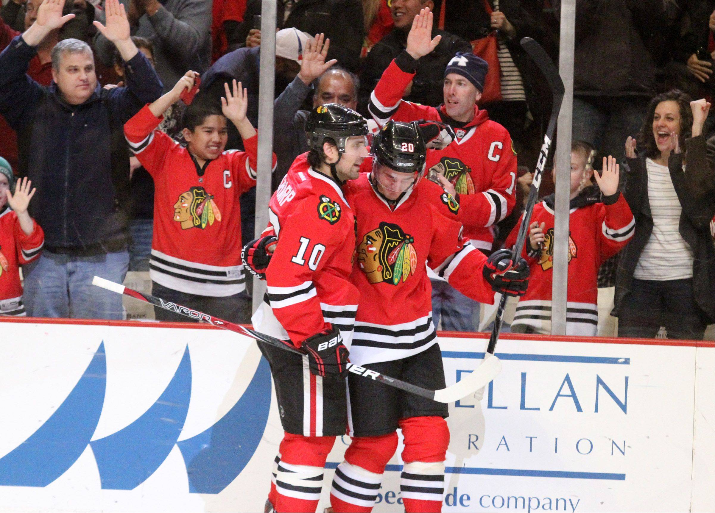 Patrick Sharp gives Brandon Saad a hand after Saad scored in the third period.