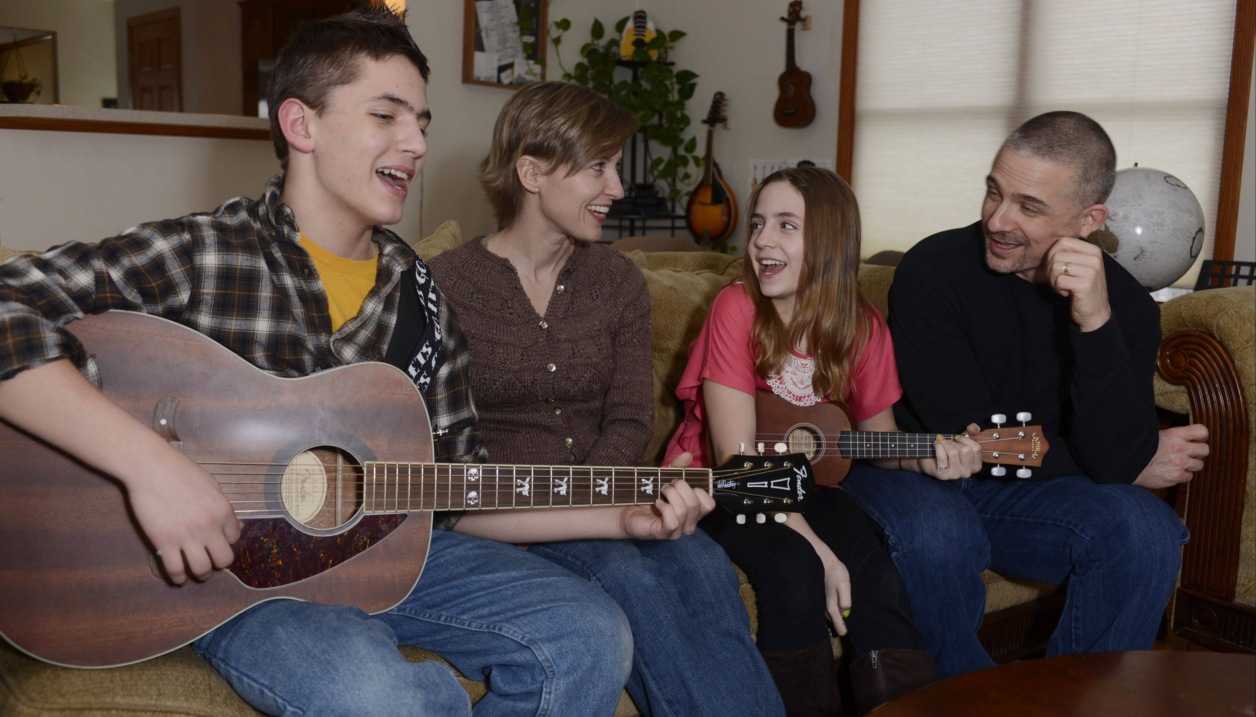 Cory and Cyndi Fosco sing with their children, Frederic (Fredo) 12, and Lily, 10, while sitting on the sofa in their Elk Grove Village home.