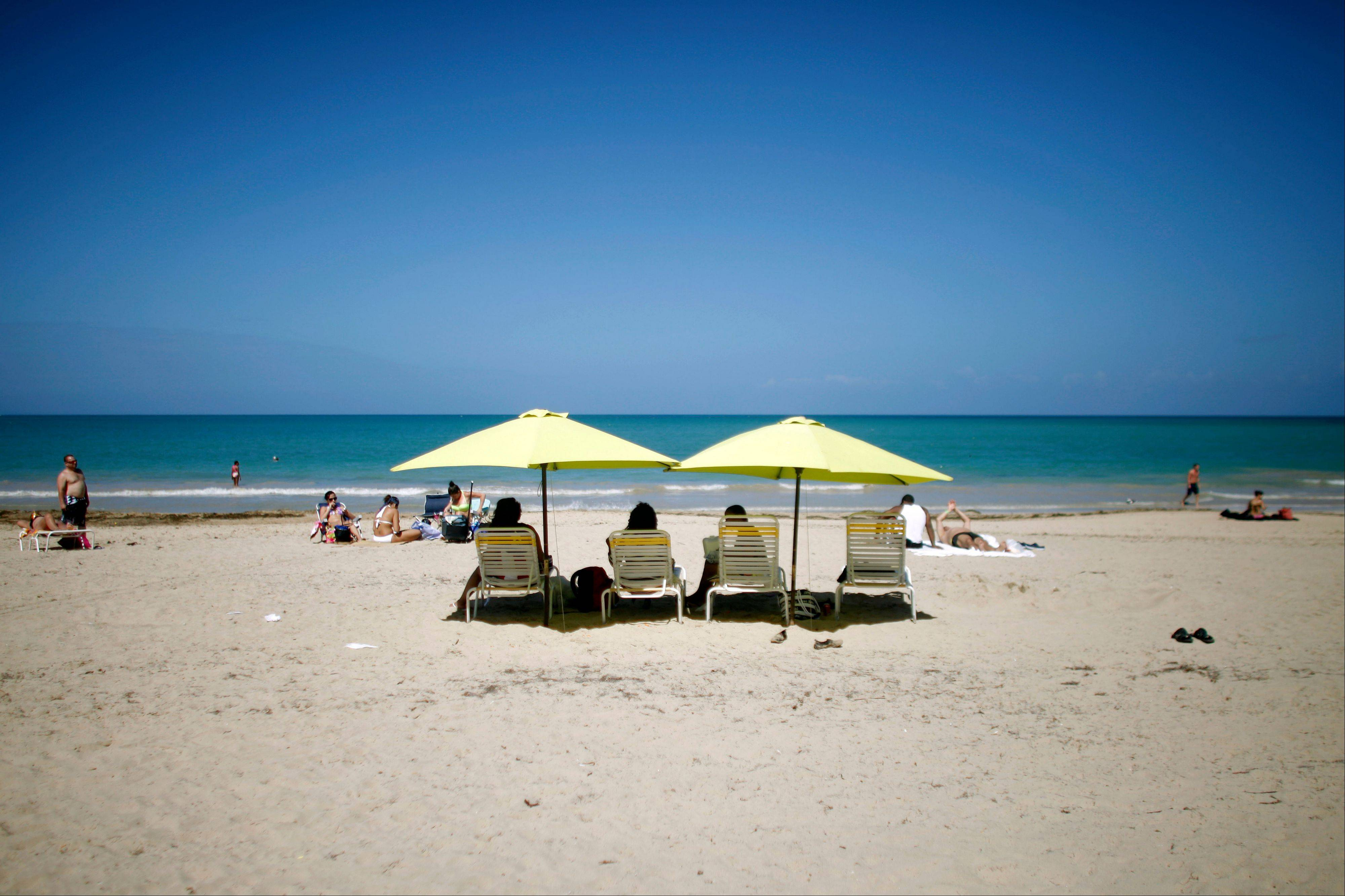 People enjoy a sunny day at the Isla Verde Beach in Carolina, Puerto Rico.