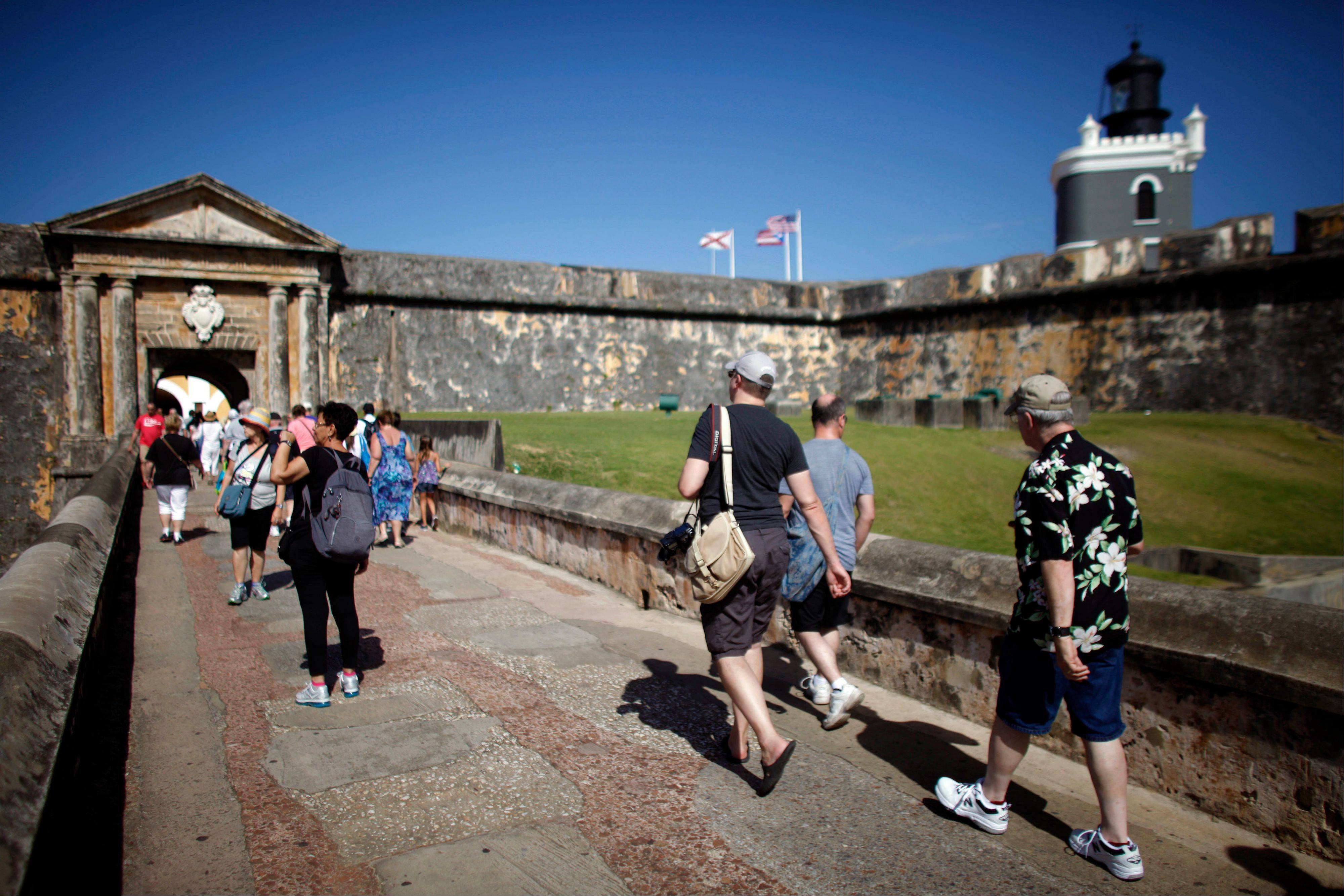 Tourists walk near the 16th-century Spanish fort called El Morro in Old San Juan, Puerto Rico.