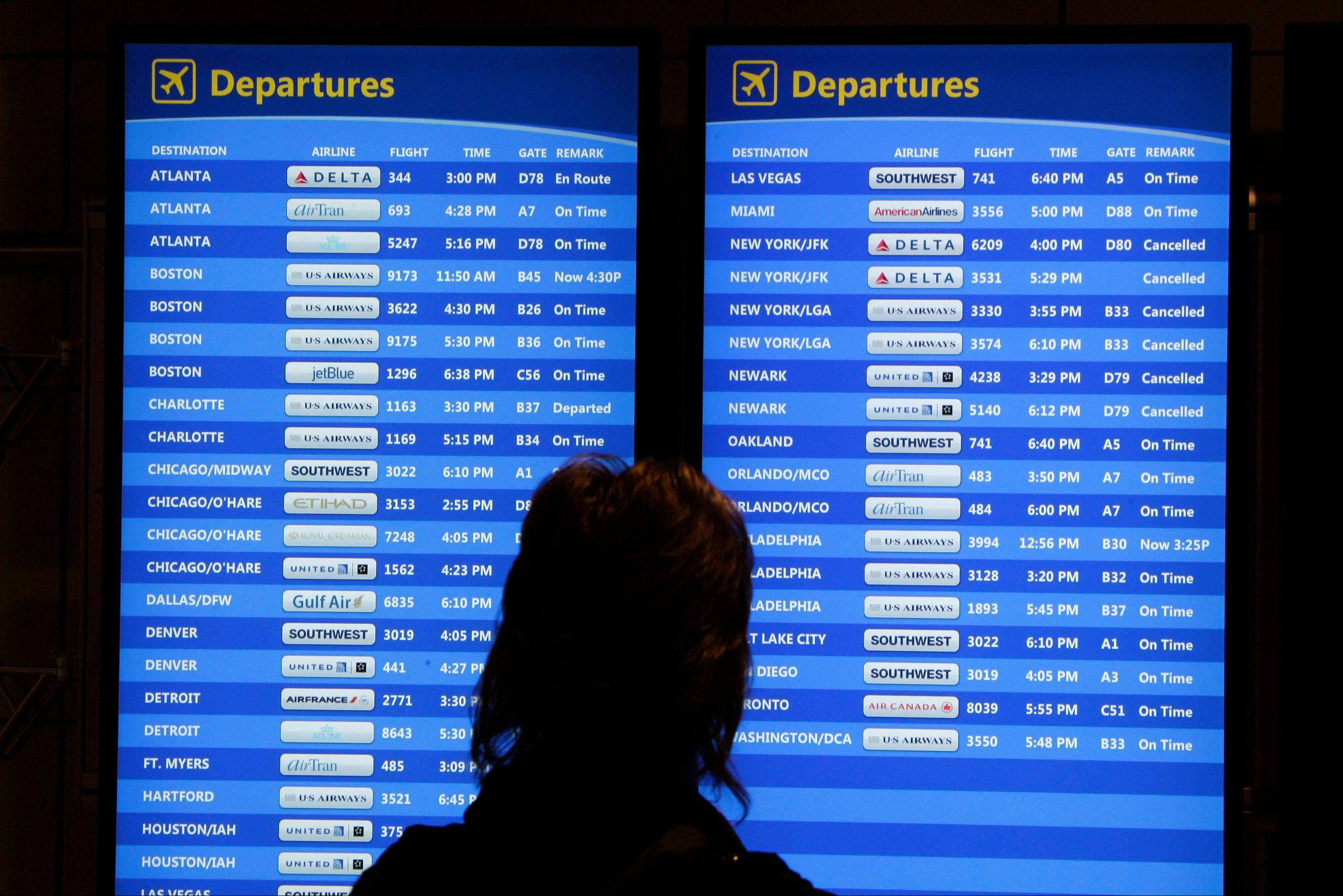 A passenger checks the departures board at Pittsburgh International Airport in Imperial, Pa. Experts say travelers planning cruises who are dependent on flights to get them to their departure ports might consider travel insurance to cover problems like missed flights.
