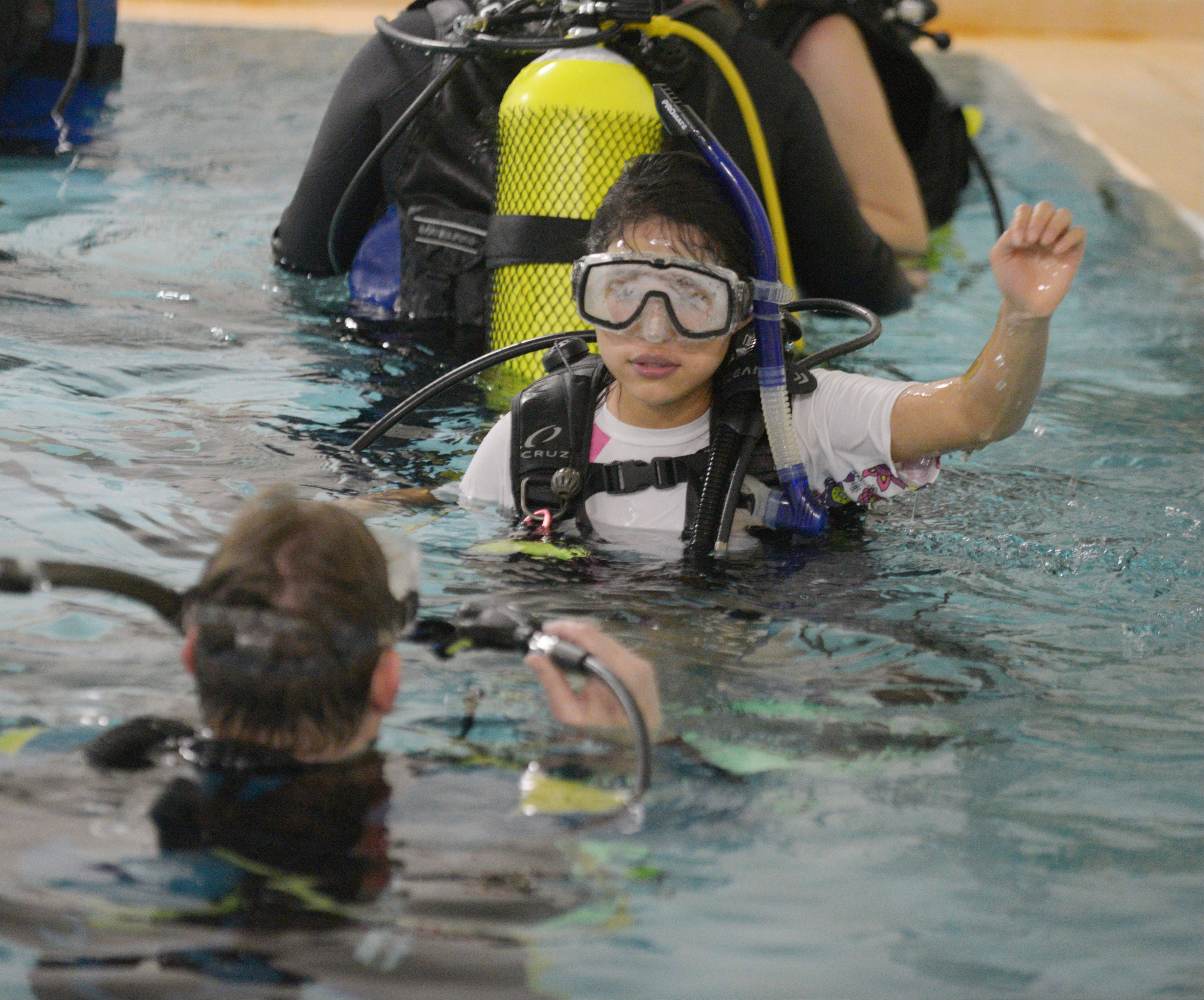Phil Seils of Buffalo Grove instructs Katia Carrilo of Aurora as she practices scuba diving hand signals Saturday in Aurora during a one-day scuba program offered by Triple Threat Mentoring and S.T.A.R.S. International, a scuba instruction nonprofit.