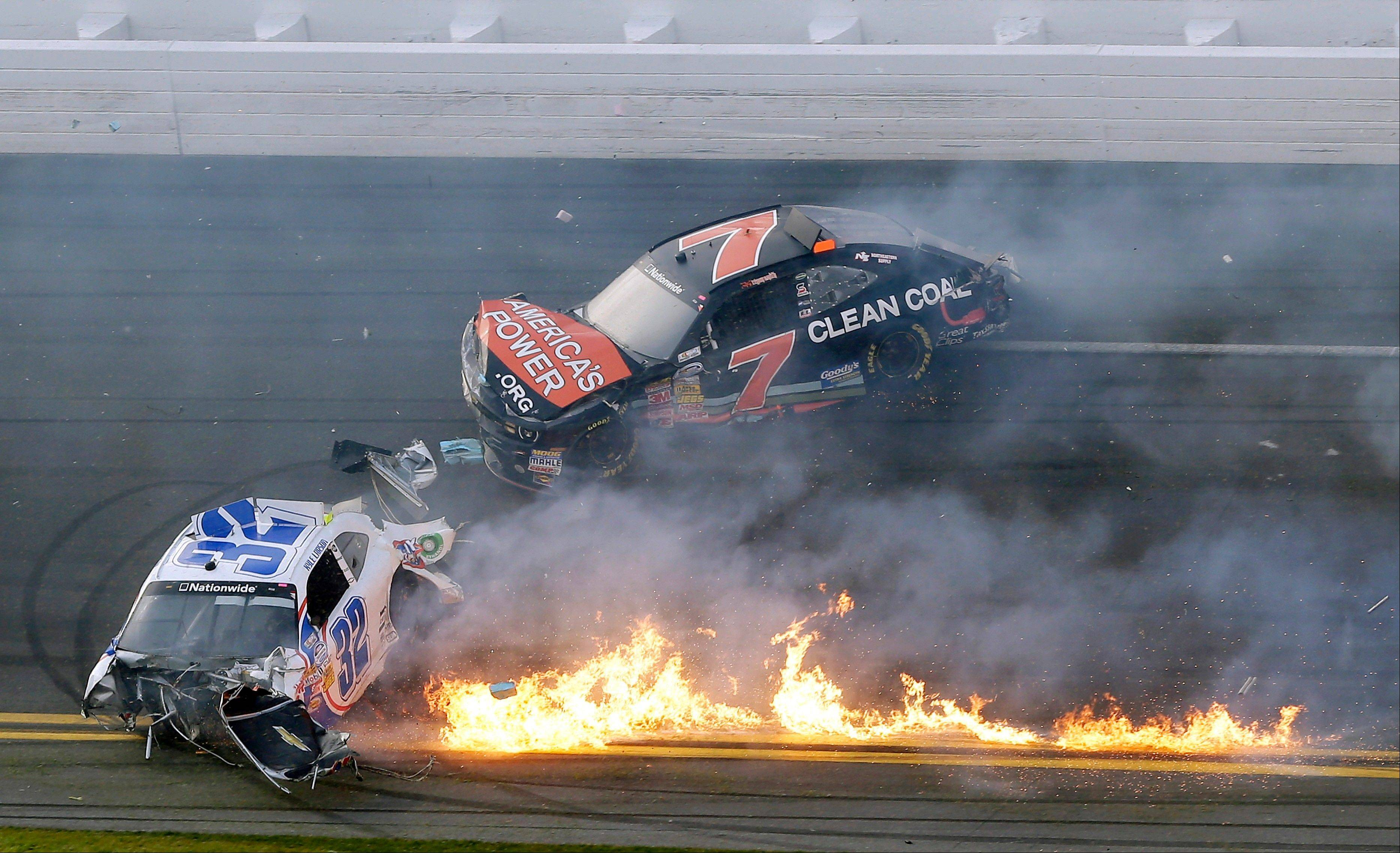 Kyle Larson's car is on fire as he slides down the track with Regan Smith after being involved in a crash at the conclusion of the NASCAR Nationwide Series auto race Saturday.