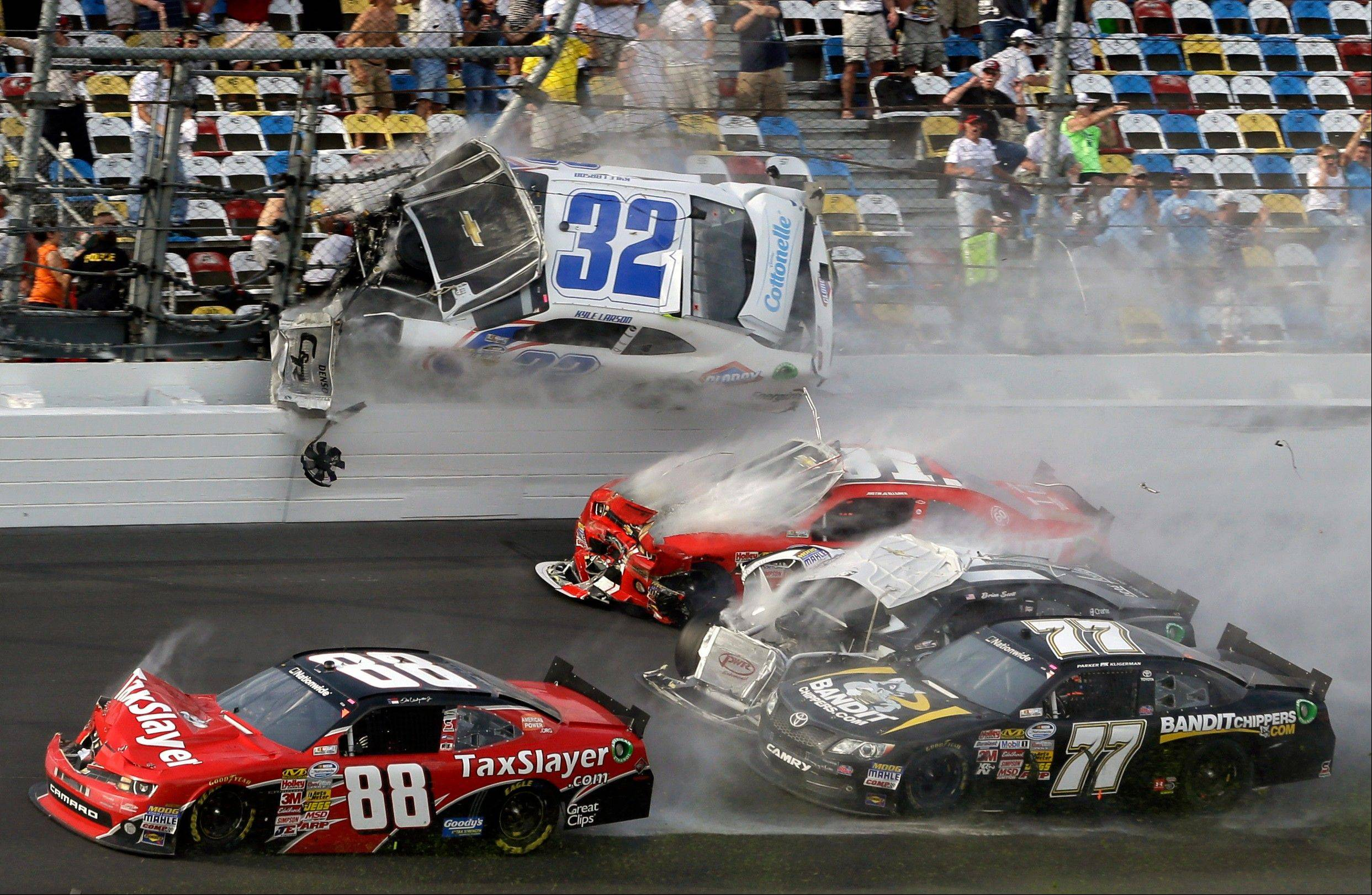 Kyle Larson (32) goes airborne into the catch fence in a multi-car crash including Dale Earnhardt Jr. (88), Parker Kligerman (77), Justin Allgaier (31) and Brian Scott (2) during the final lap of the NASCAR Nationwide Series auto race at Daytona International Speedway.