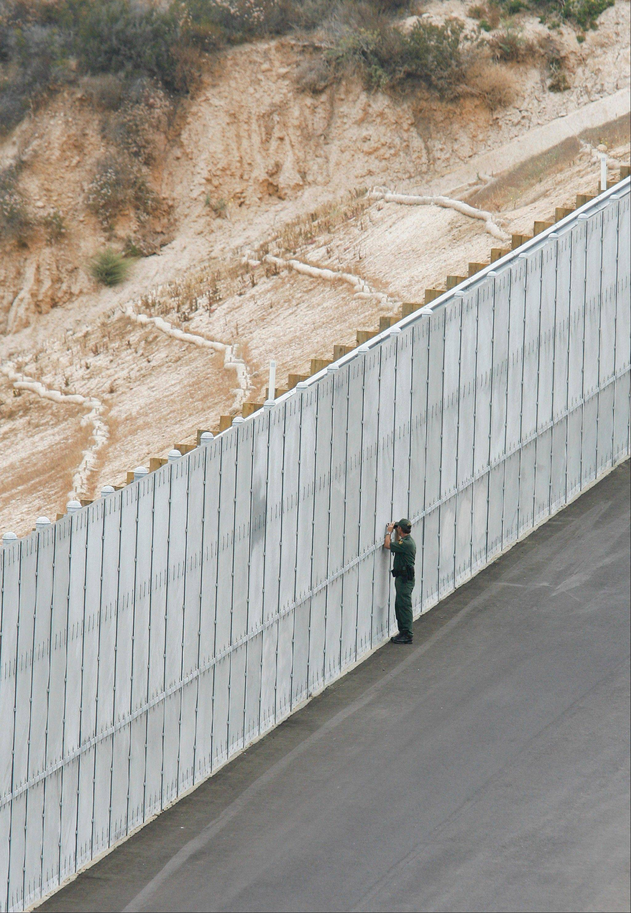 "Associated Press/July 6, 2009A border patrol agent peers through a section of fence in San Diego that is part of the ""Smuggler's Gulch"" area."