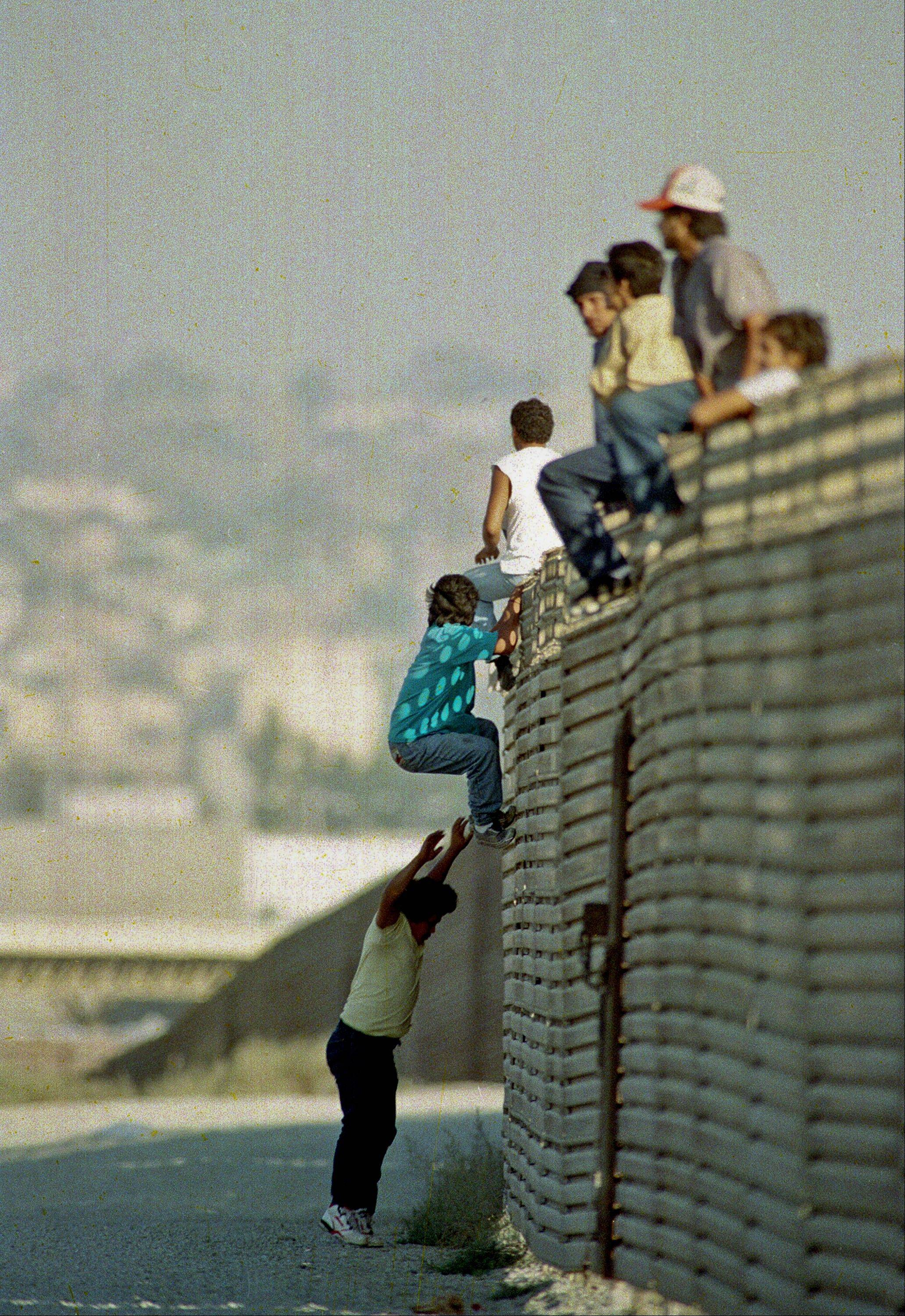Associated Press/Oct. 14 1991A group of illegal Mexican immigrants jump from a border fence to enter the United States, near Tijuana, Mexico.