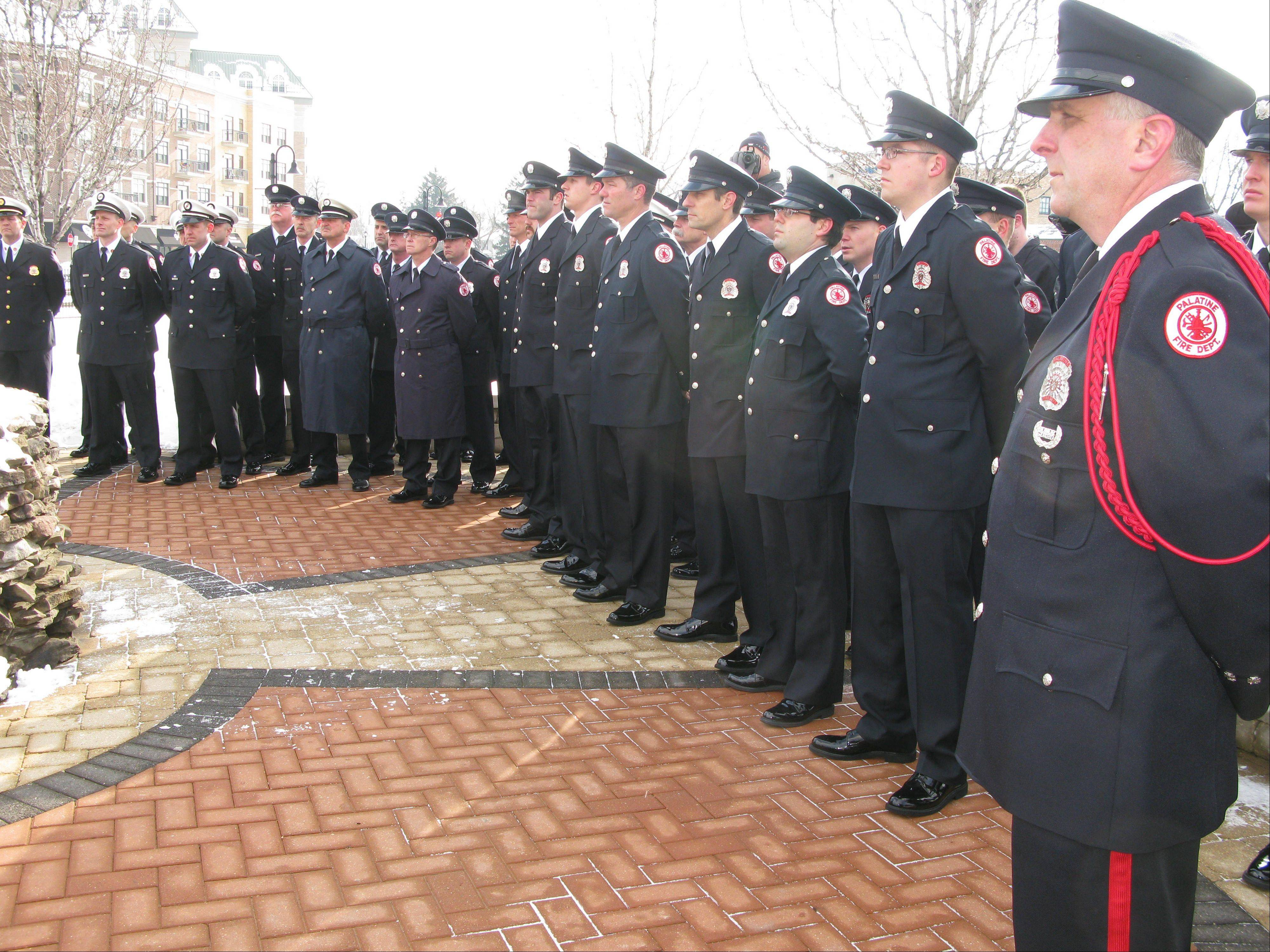Firefighters from Palatine and other area fire departments stand during a ceremony to honor the memory of three fallen Palatine volunteer firefighters Saturday on the 40th anniversary of their deaths.