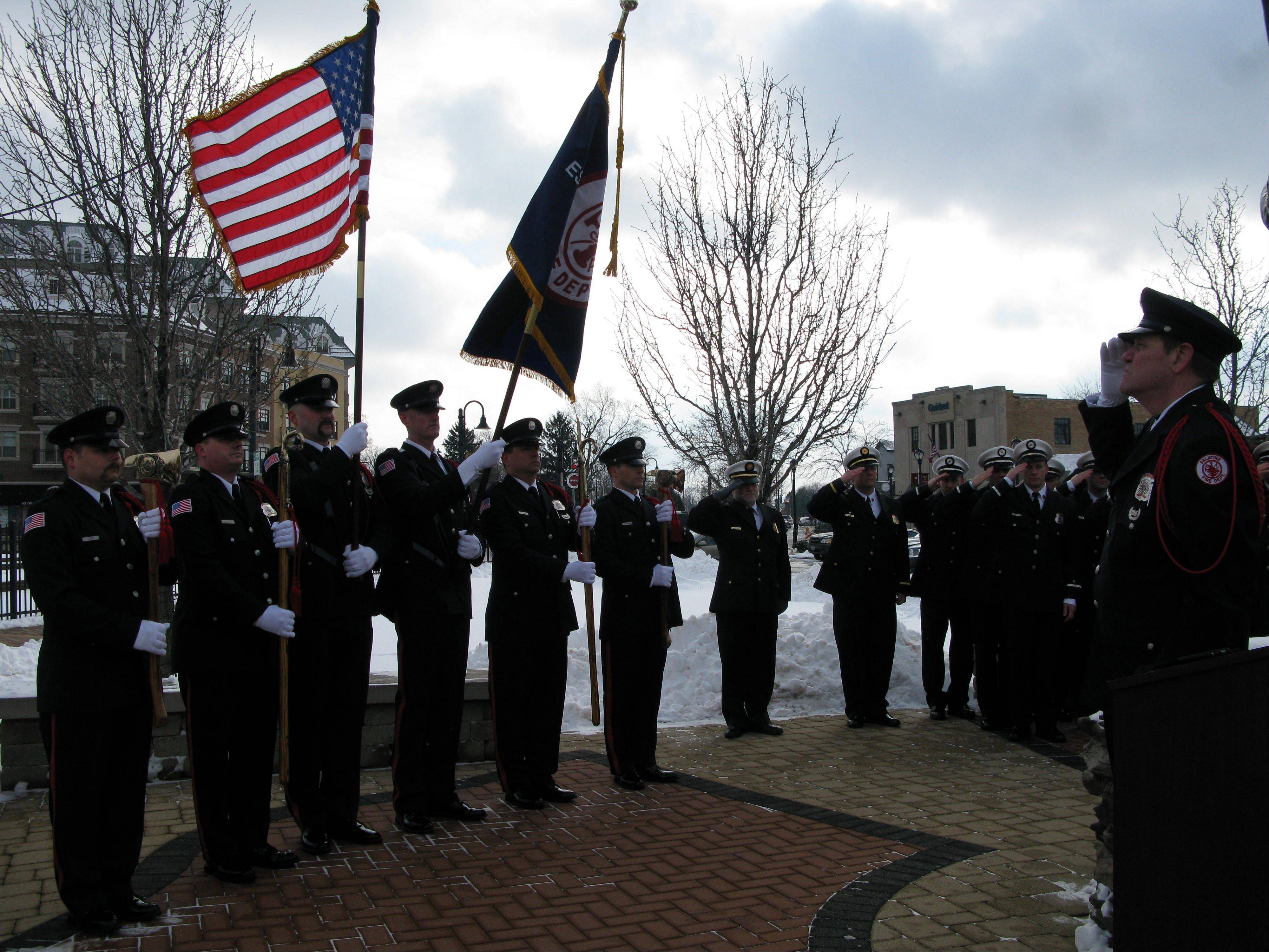 Retired firefighter Mark Hallett, right, salutes the flag carried by the Palatine Fire Department Honor Guard Saturday during a ceremony honoring the sacrifice made by three volunteer firefighters, John Wilson, Richard Freeman and Warren Ahlgrim, who perished during a fire rescue on Feb. 23, 1973.