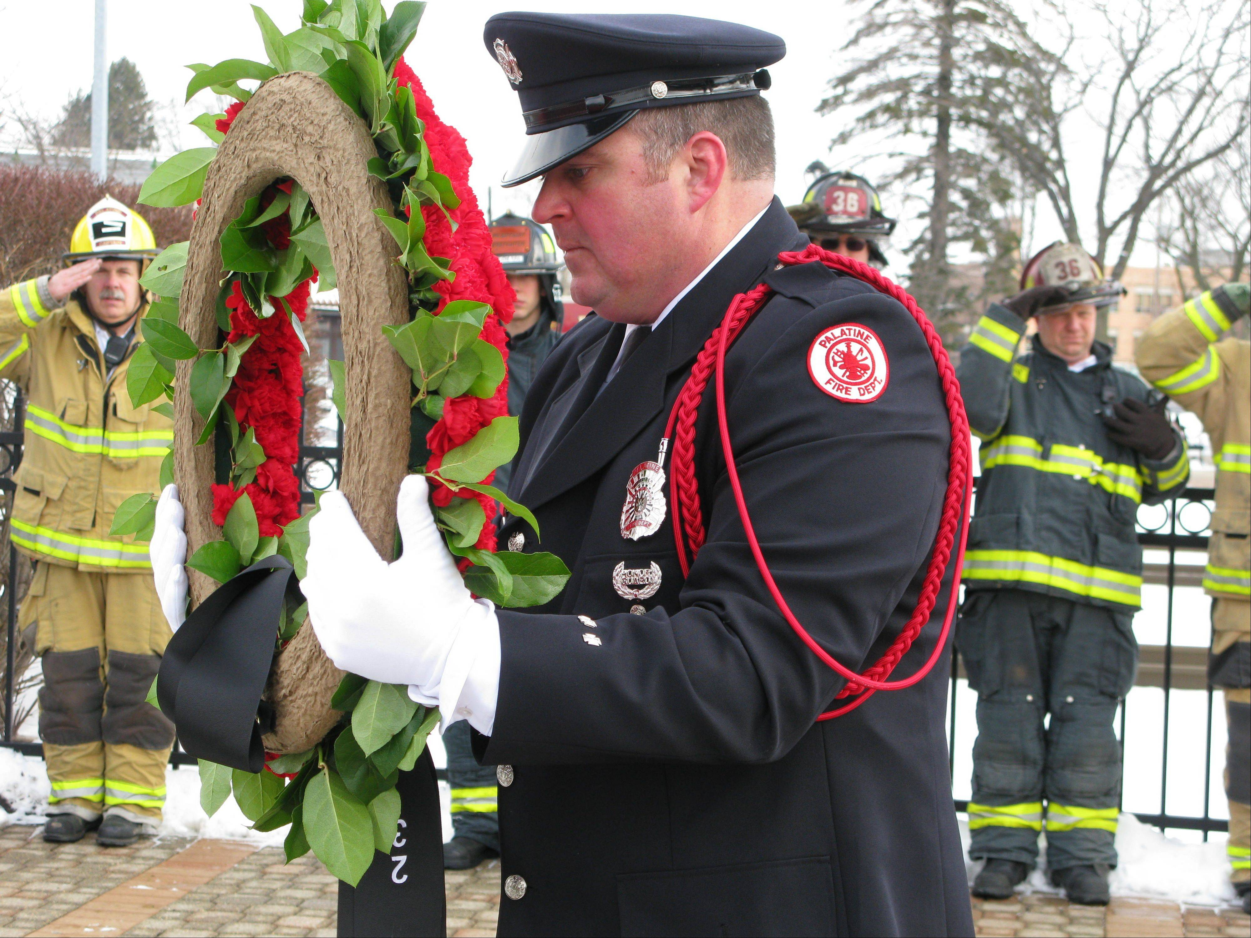 Palatine firefighter Dale Stankiewicz carries a wreath to place on the memorial for three fallen volunteer firefighters, John Wilson, Richard Freeman and Warren Ahlgrim, who perished during a fire rescue on Feb. 23, 1973. Roughly 200 people, including firefighters from several area departments, attended a ceremony Saturday at the Firefighters Memorial in downtown Palatine to honor their memory and commemorate the 40th anniversary of their deaths.