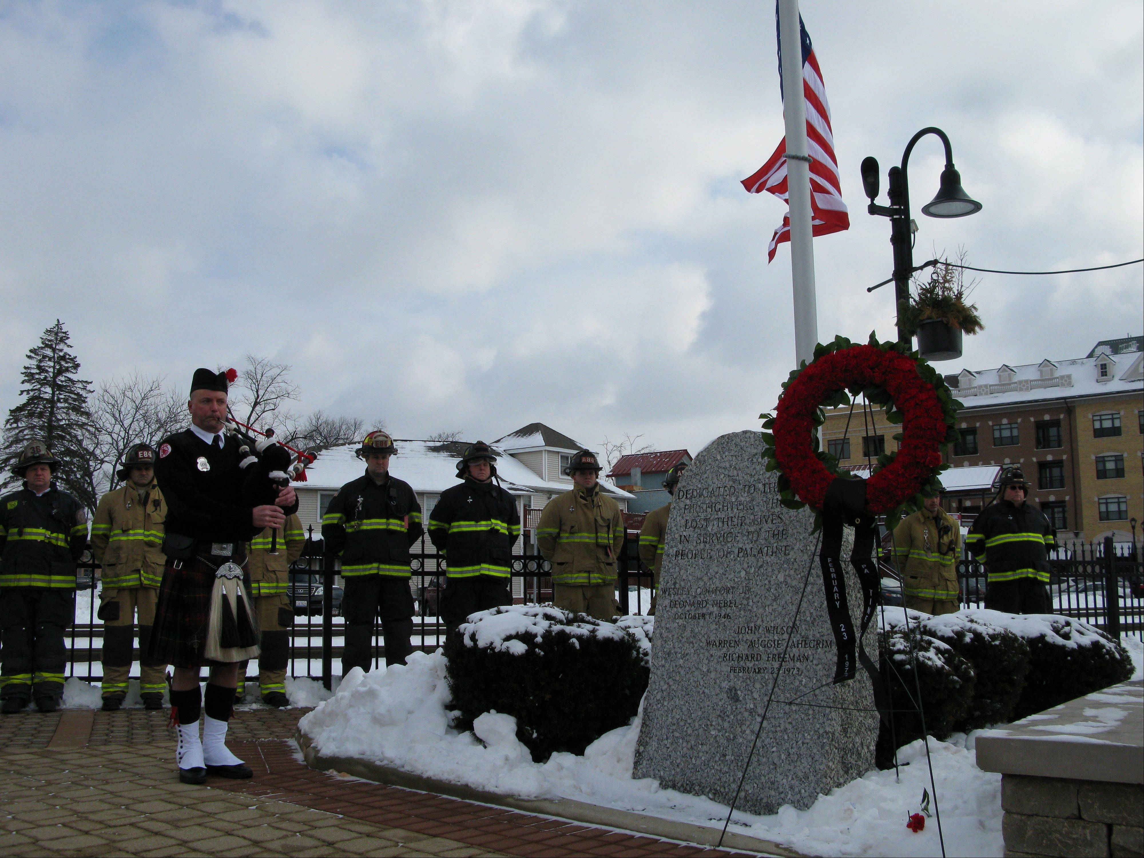 A bagpiper plays after the placing of a wreath on the memorial for three fallen volunteer Palatine firefighters, John Wilson, Richard Freeman and Warren Ahlgrim, who perished during a fire rescue on Feb. 23, 1973. Roughly 200 people, including firefighters from several area departments, attended a ceremony Saturday at the Firefighters Memorial in downtown Palatine to honor their memory and commemorate the 40th anniversary of their deaths.