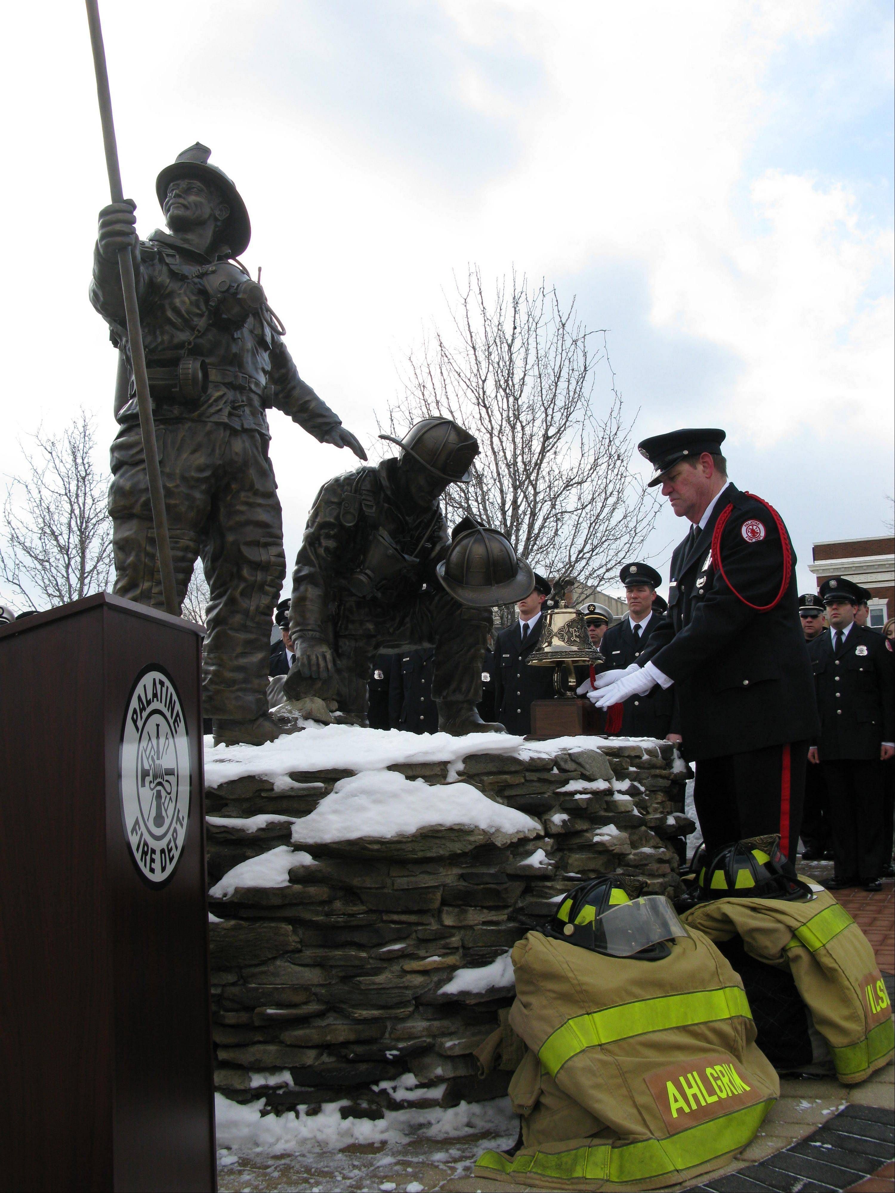 Retired firefighter Mark Hallett sounds the bell three times for each of the fallen volunteer Palatine firefighters, John Wilson, Richard Freeman and Warren Ahlgrim, who perished during a fire rescue on Feb. 23, 1973.