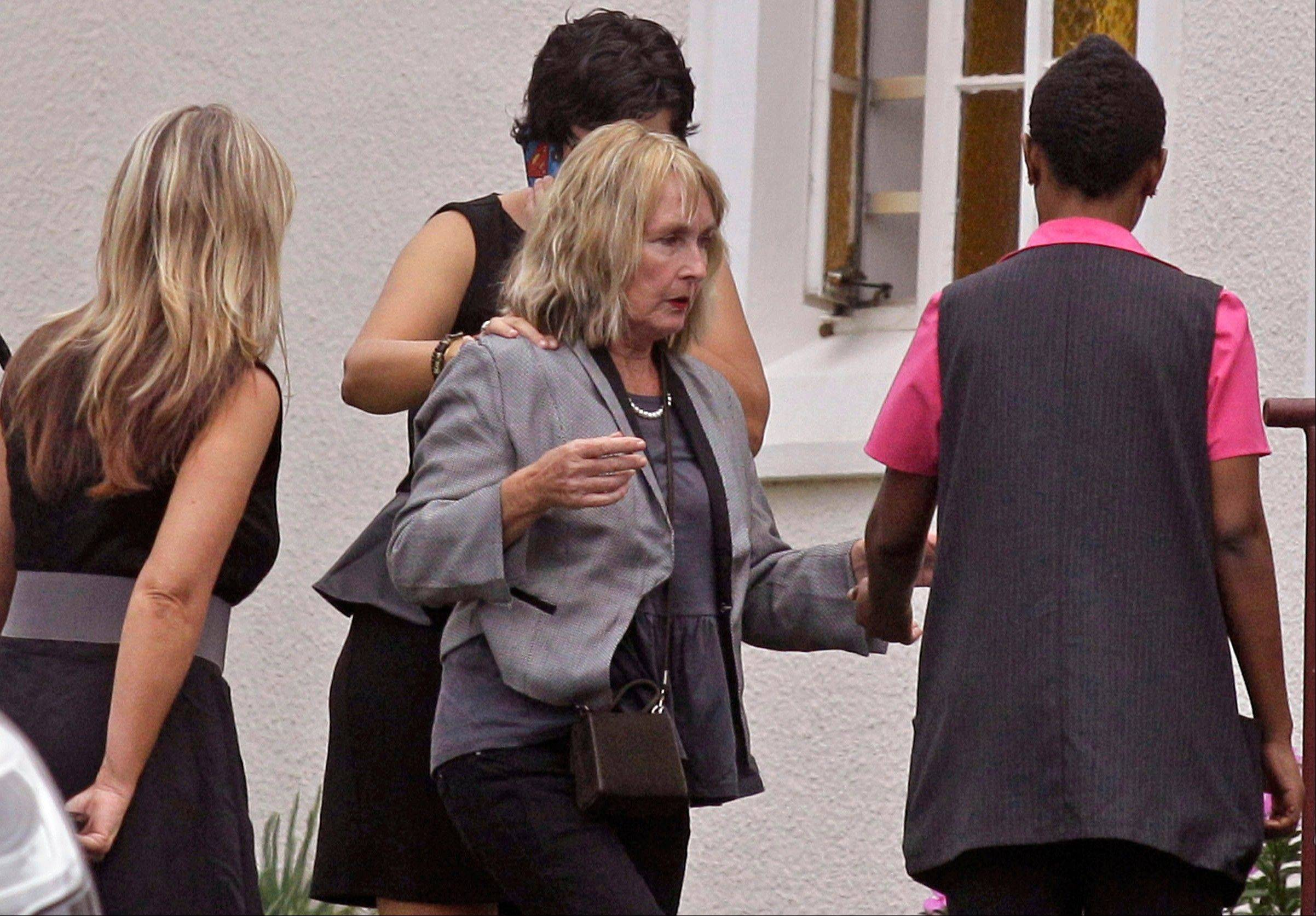 June Steenkamp, center, the mother of Reeva Steenkamp, arrives for her funeral Tuesday in Port Elizabeth, South Africa. The Steenkamp family has struggled with it's own grief and harbors misgivings about efforts by the Pistorius family to reach out to them with condolences.