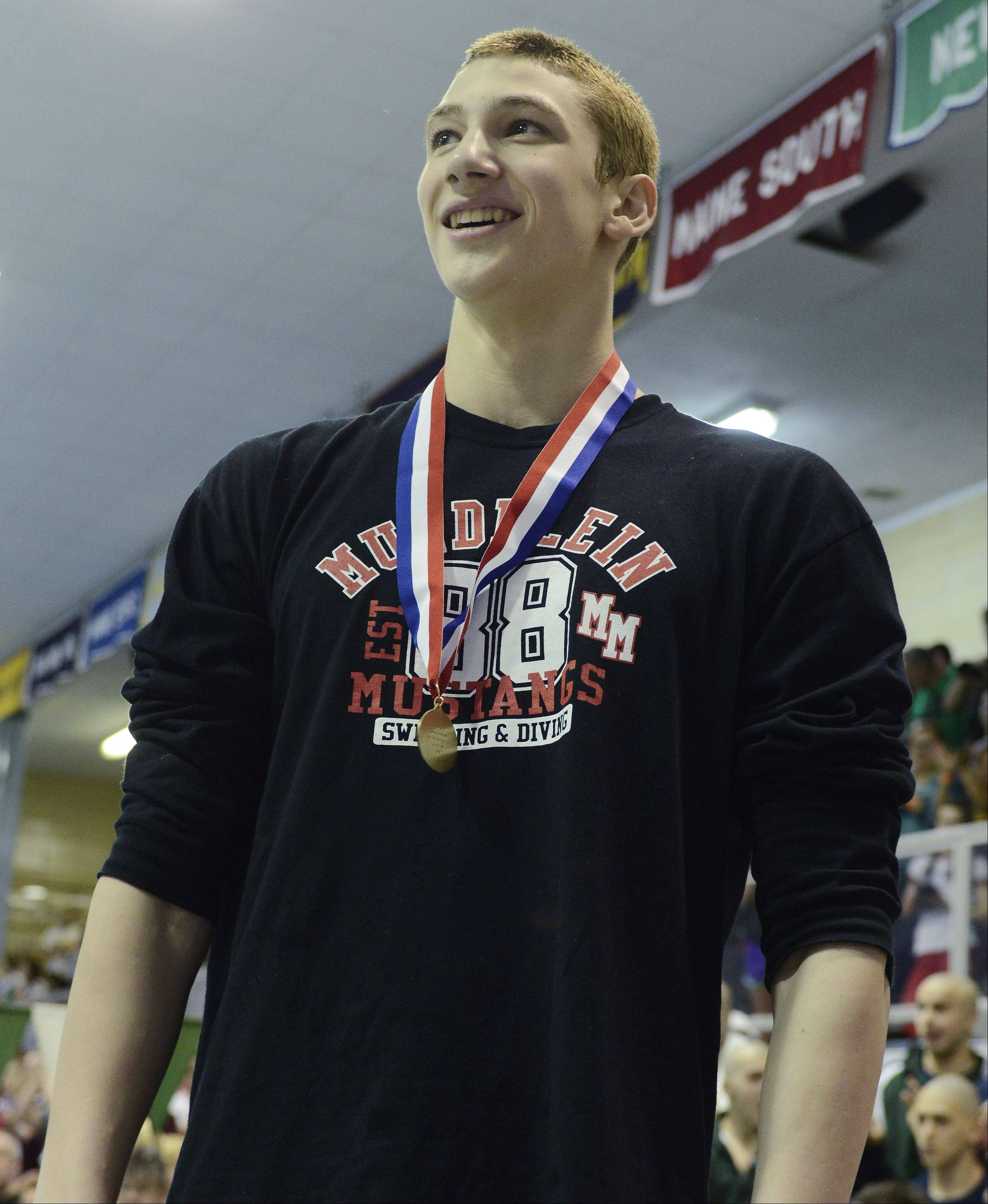 Mundelein's Connor Black smiles on the award stand after setting national of 46.71 in the 100-yard butterfly in the boys swimming state finals at New Trier High School in Winnetka on Saturday.