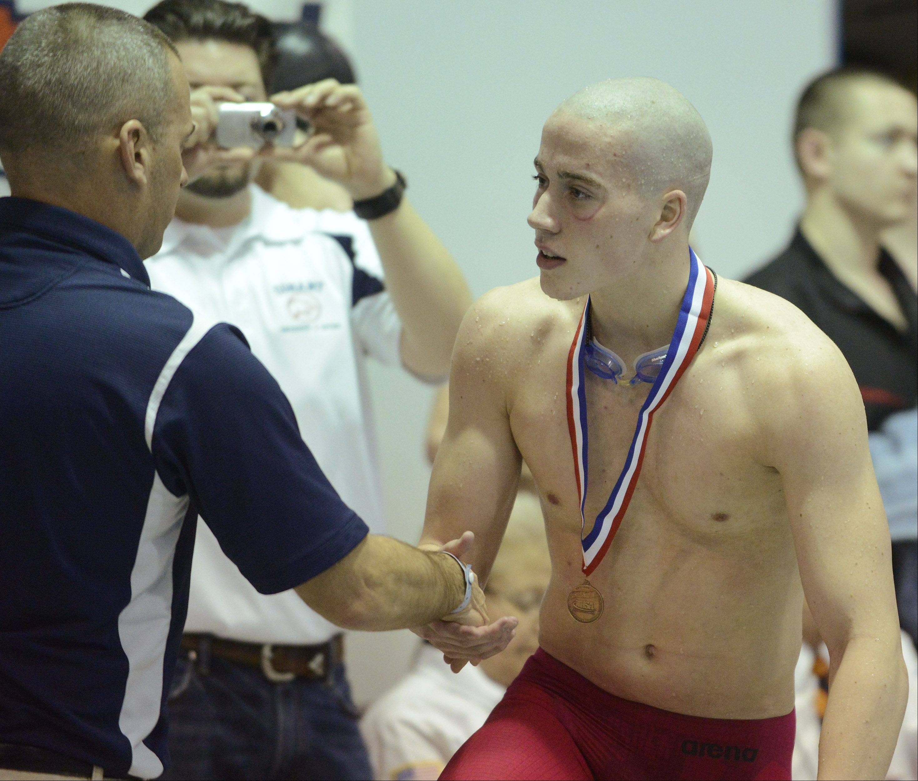 Conant's Jonathon Burke receives his medal after finishing third in the 500-yard freestyle during the state finals at New Trier High School in Winnetka on Saturday.