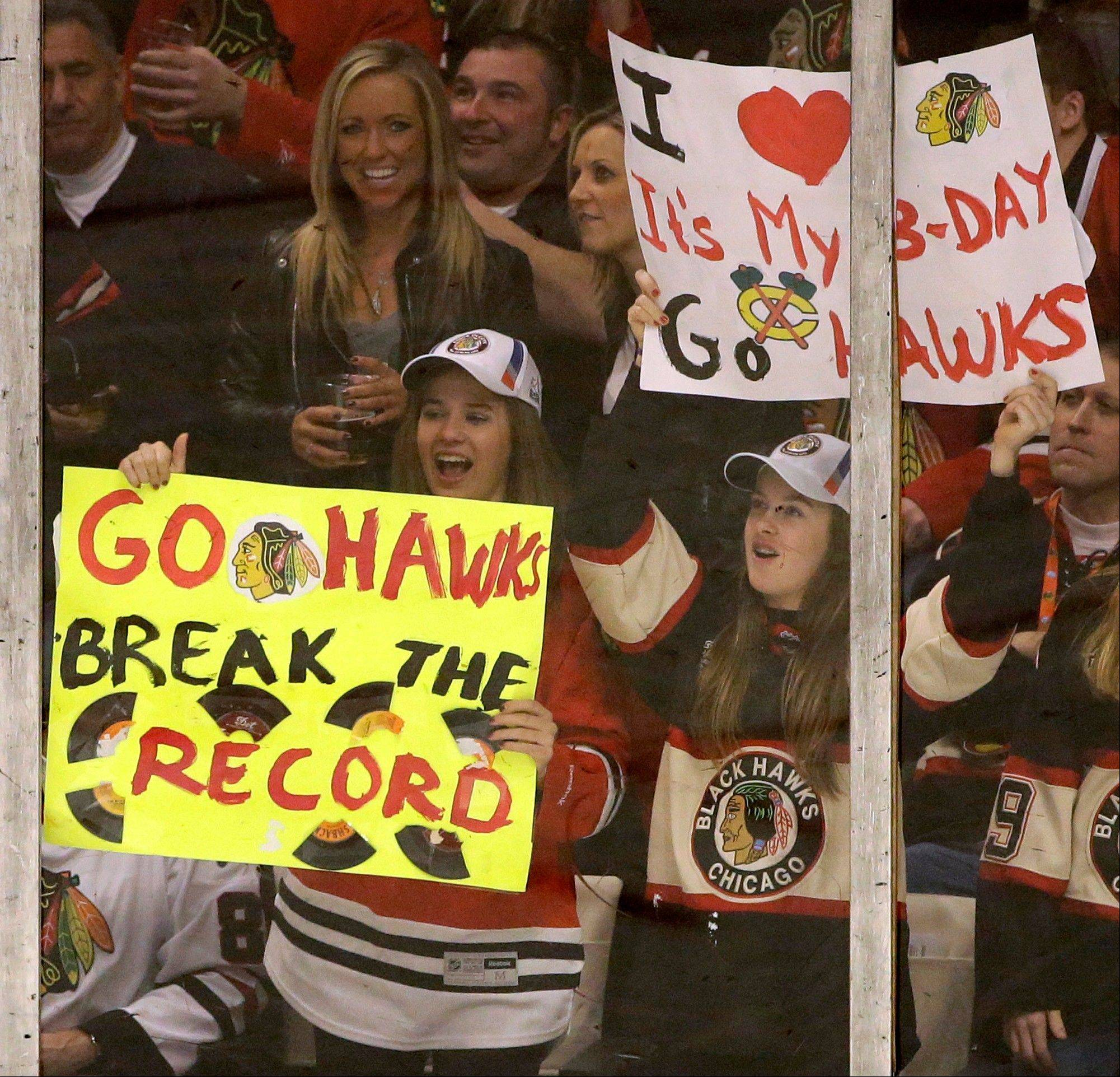 Chicago Blackhawks fans hold signs during thethird period of an NHL hockey game between the Chicago Blackhawks and the San Jose Sharks in Chicago, Friday, Feb. 22, 2013. The Blackhawks won 2-1.
