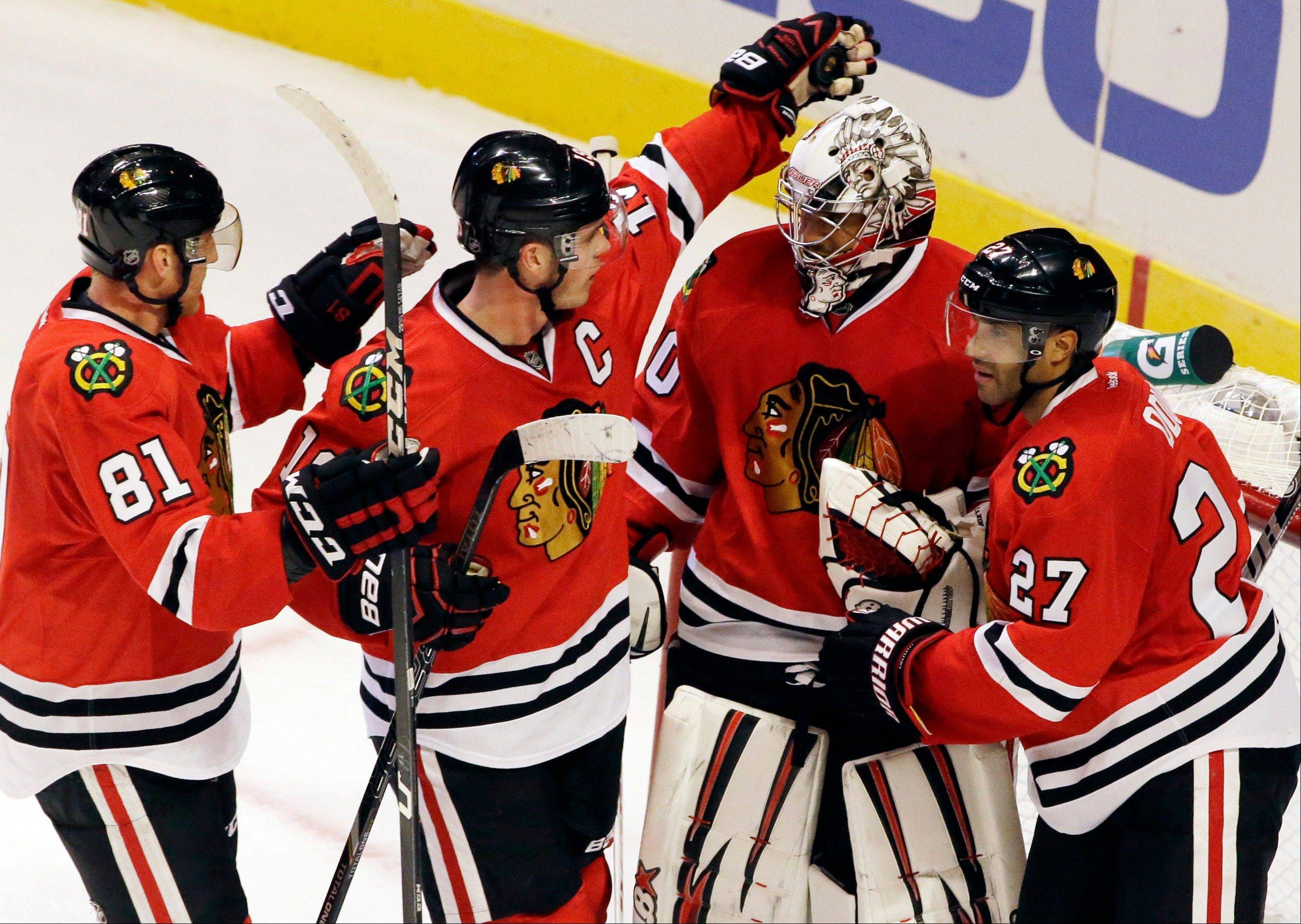 Chicago Blackhawks goalie Ray Emery, second from right, celebrates with Jonathan Toews (19), Marian Hossa (81) and Johnny Oduya (27) after the Blackhawks defeated the San Jose Sharks 2-1 during an NHL hockey game in Chicago, Friday, Feb. 22, 2013.