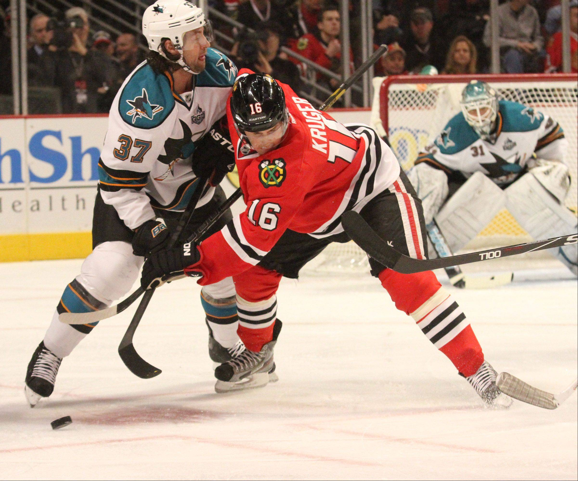 Blackhawk Marcus Kruger faces off against San Jose Sharks right wing Adam Burish.