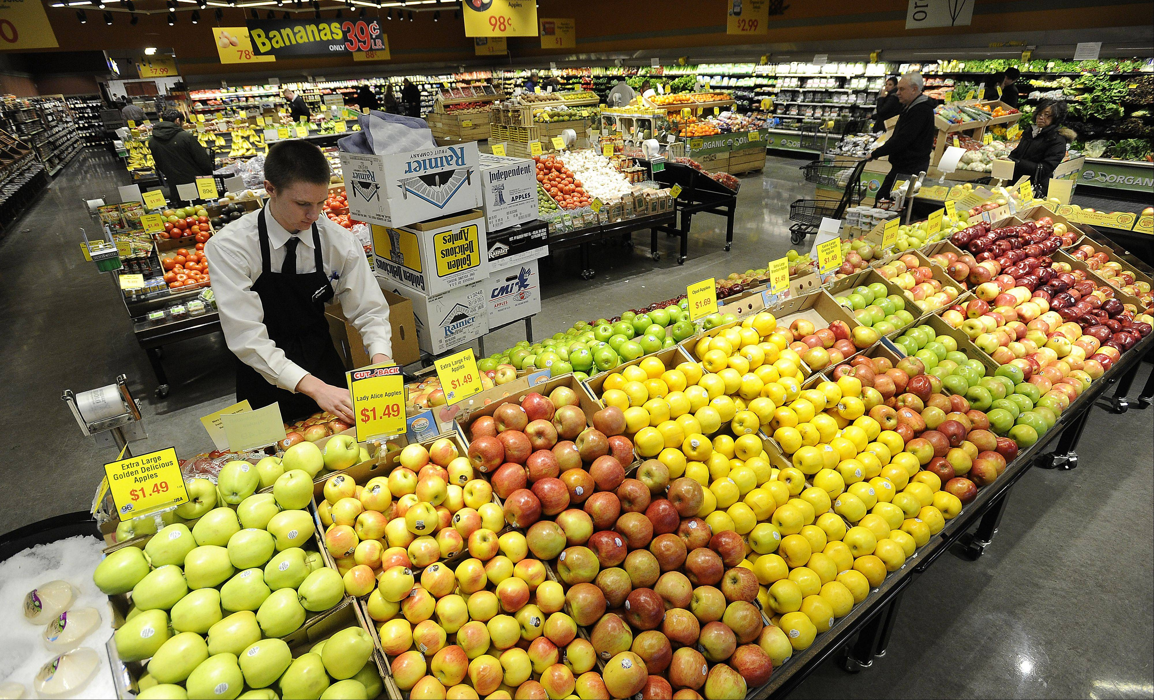 Produce clerk Charlie Gimmler of Palatine stocks apples and other produce at Mariano's in Palatine. Fresh produce is in high demand in the suburbs, so grocers pay special attention to it.
