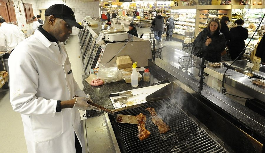 Avery Osby of Hoffman Estates grills some meat for a customer at Mariano's in Palatine. There's a seating area for customers to eat inside the store.