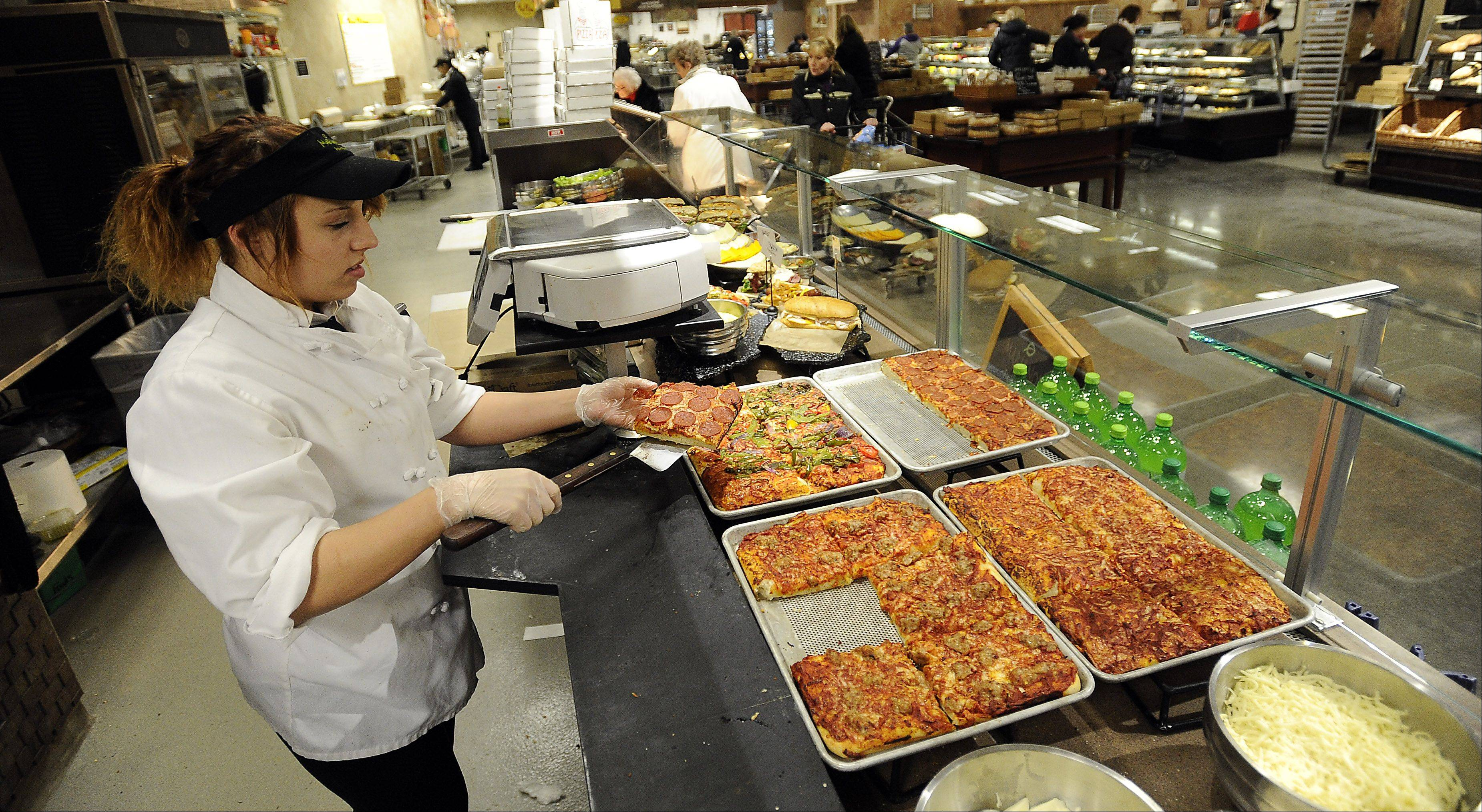 Cori Baum of Hoffman Estates serves pizza at Mariano's in Palatine. Hot food offerings provide easy dinner options for suburban customers.