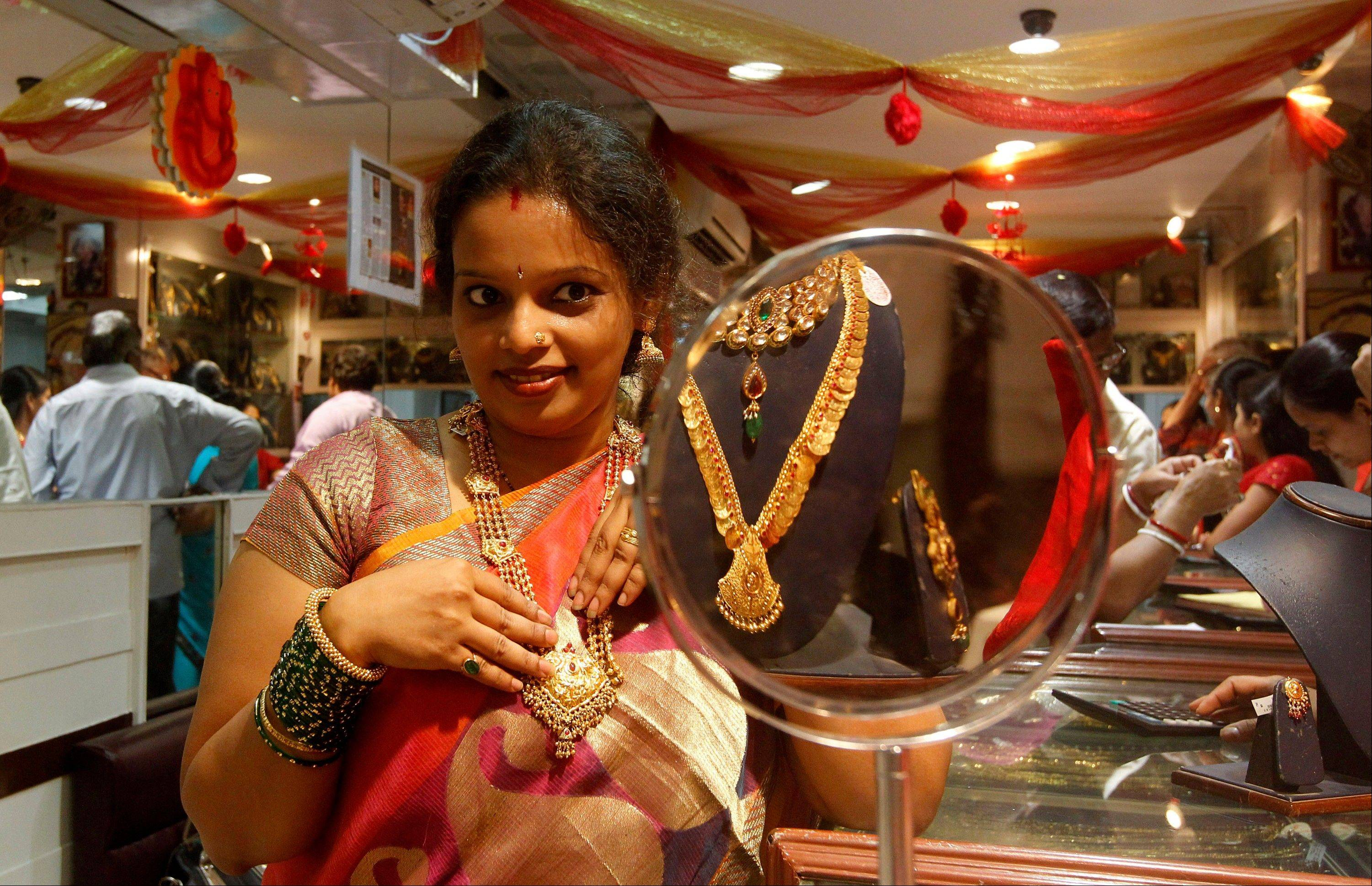 An Indian woman looks into a mirror as she tries out gold jewelry at a shop in Mumbai, India. The unquenchable appetite for gold coins, bars and jewelry has swelled India's trade deficit and weakened its currency, making crucial imports such as fuel more expensive.