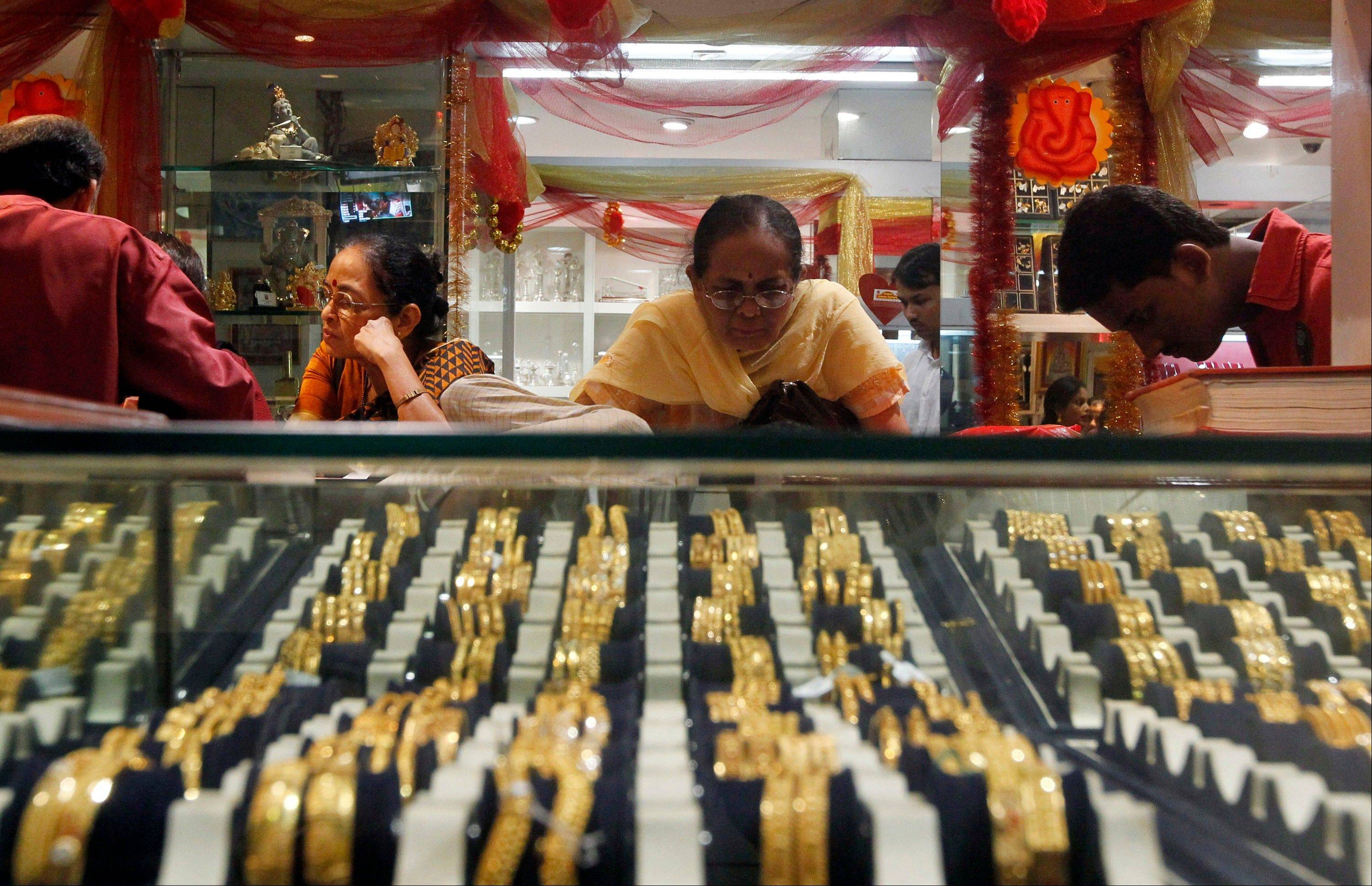 An Indian woman looks at a display of gold jewelry at a shop in Mumbai, India. Nowadays, India is by far the world's biggest buyer of gold, which despite its rising value, is an increasing drain on an economy that is growing too slowly to reduce widespread poverty.