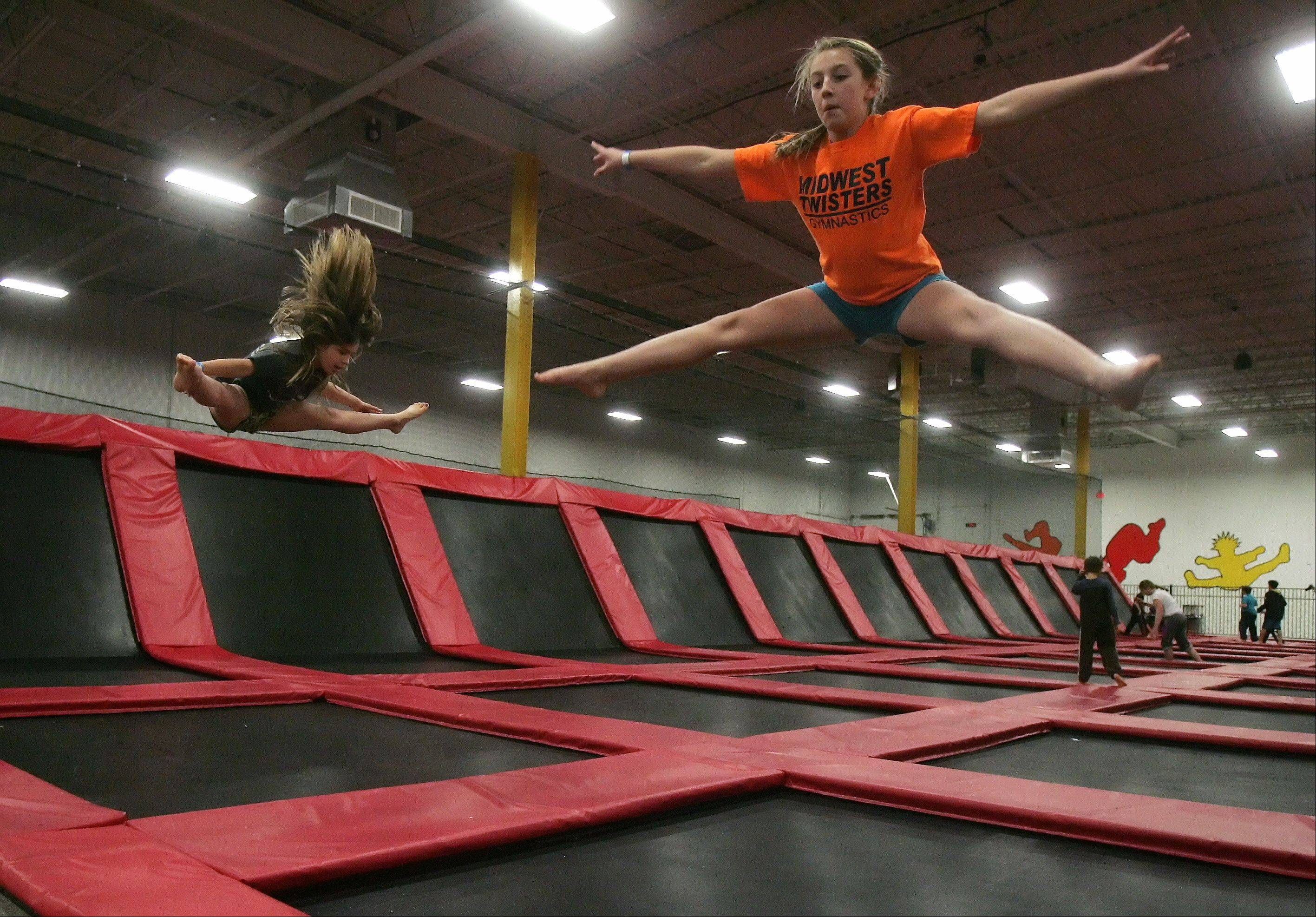 Emma Lloyd, right, and Sophia Cepeda, of Deerfield, practice tricks as they jump around at Xtreme Trampolines in Buffalo Grove. The entertainment center offers an active alternative for kids in the suburbs.