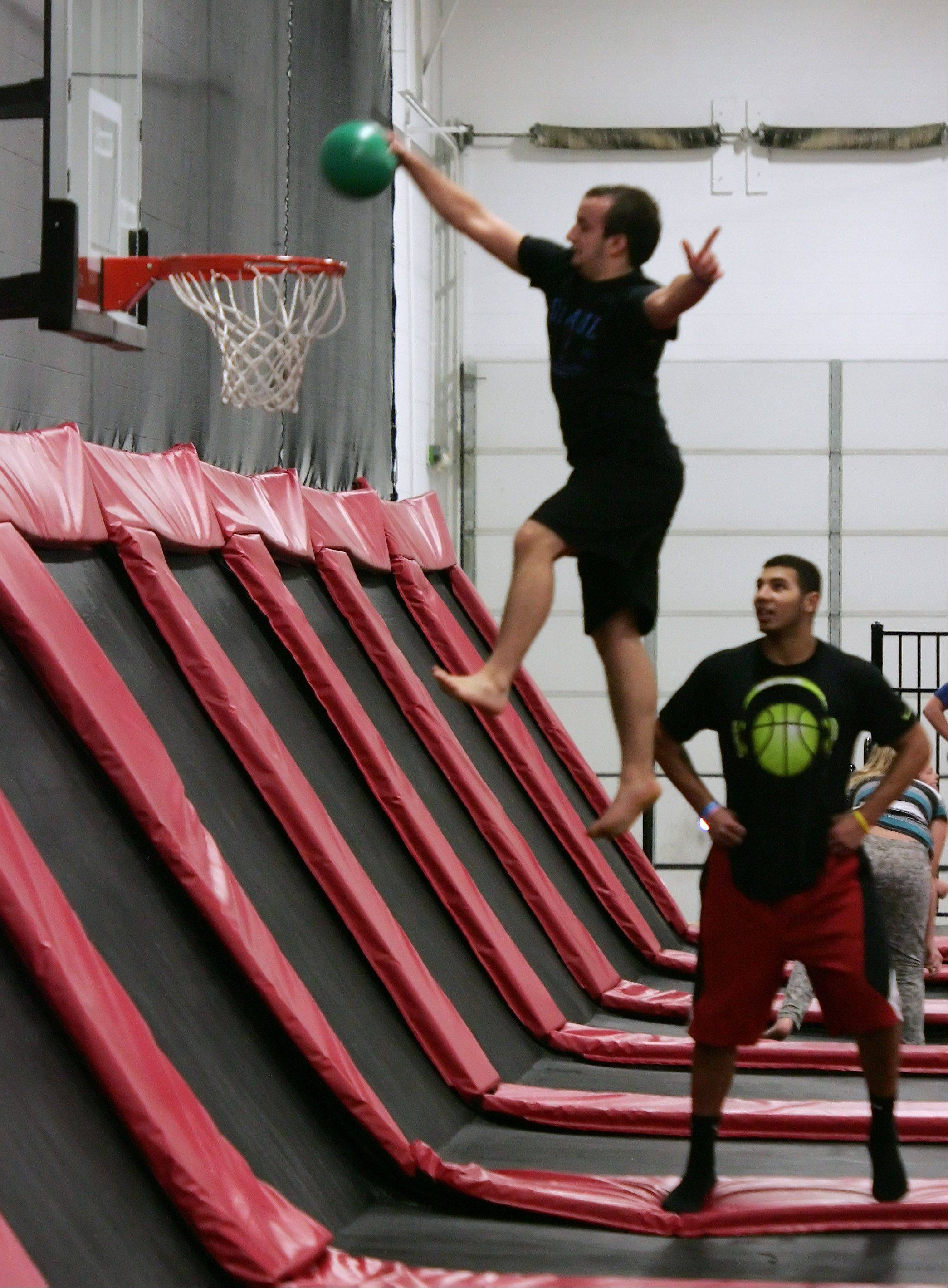 Merza Merza, 18, of Addison, dunks a ball as he jumps around at Xtreme Trampolines in Buffalo Grove. The entertainment center offers an active alternative for kids in the suburbs.