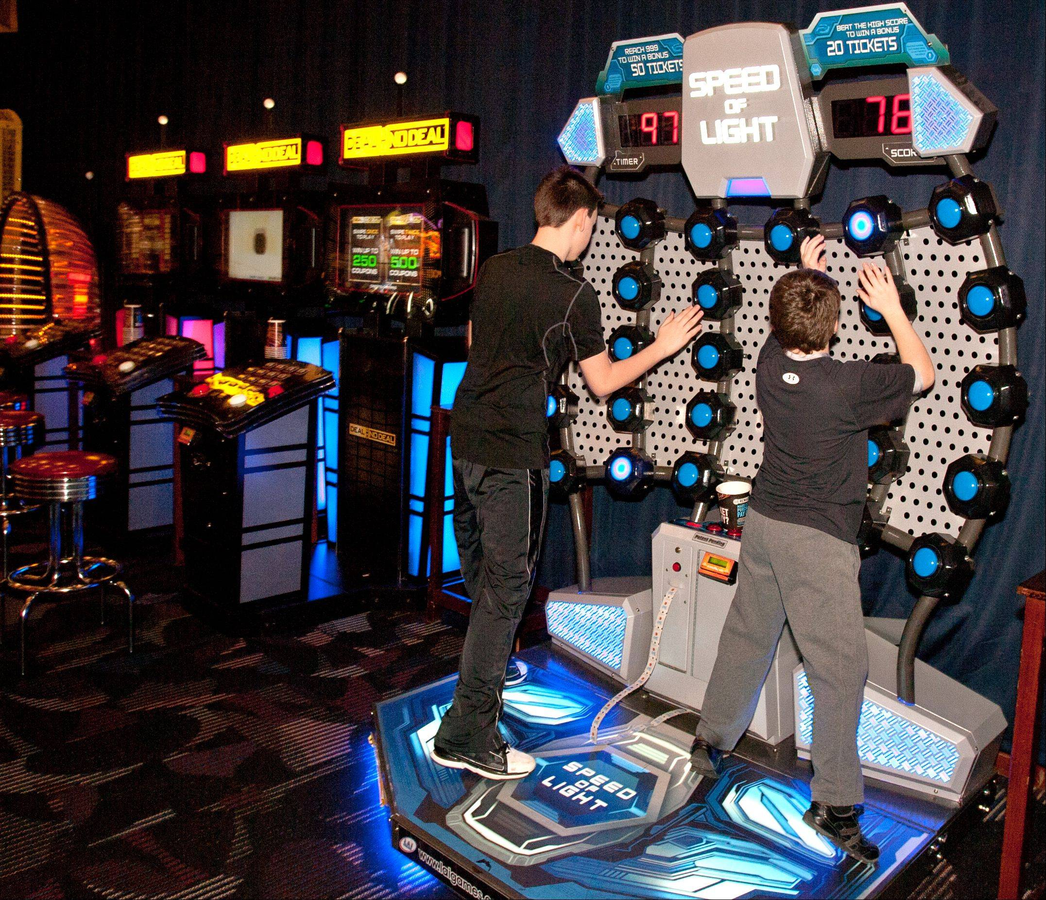 Andrew Gorski, 12, of Plainfield, left, and Griffin Coleman, 12, of Plainfield, right, play Speed of Light, one of the popular interactive video games that gets kids moving at Dave and Buster's in Addison.