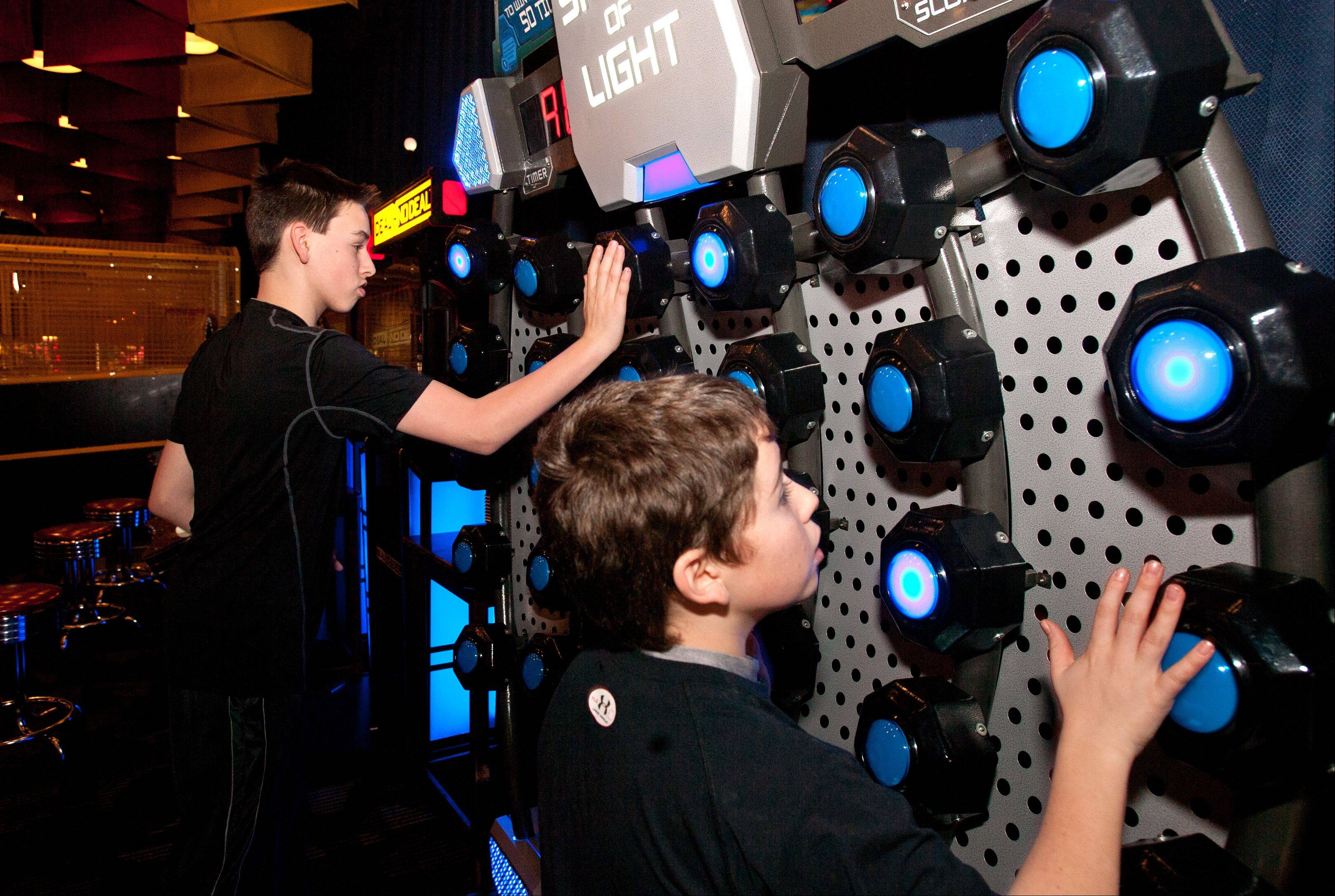 Andrew Gorski, 12, of Plainfield, left, and Griffin Coleman, 12, of Plainfield, right, play Speed of Light at Dave and Buster's in Addison.