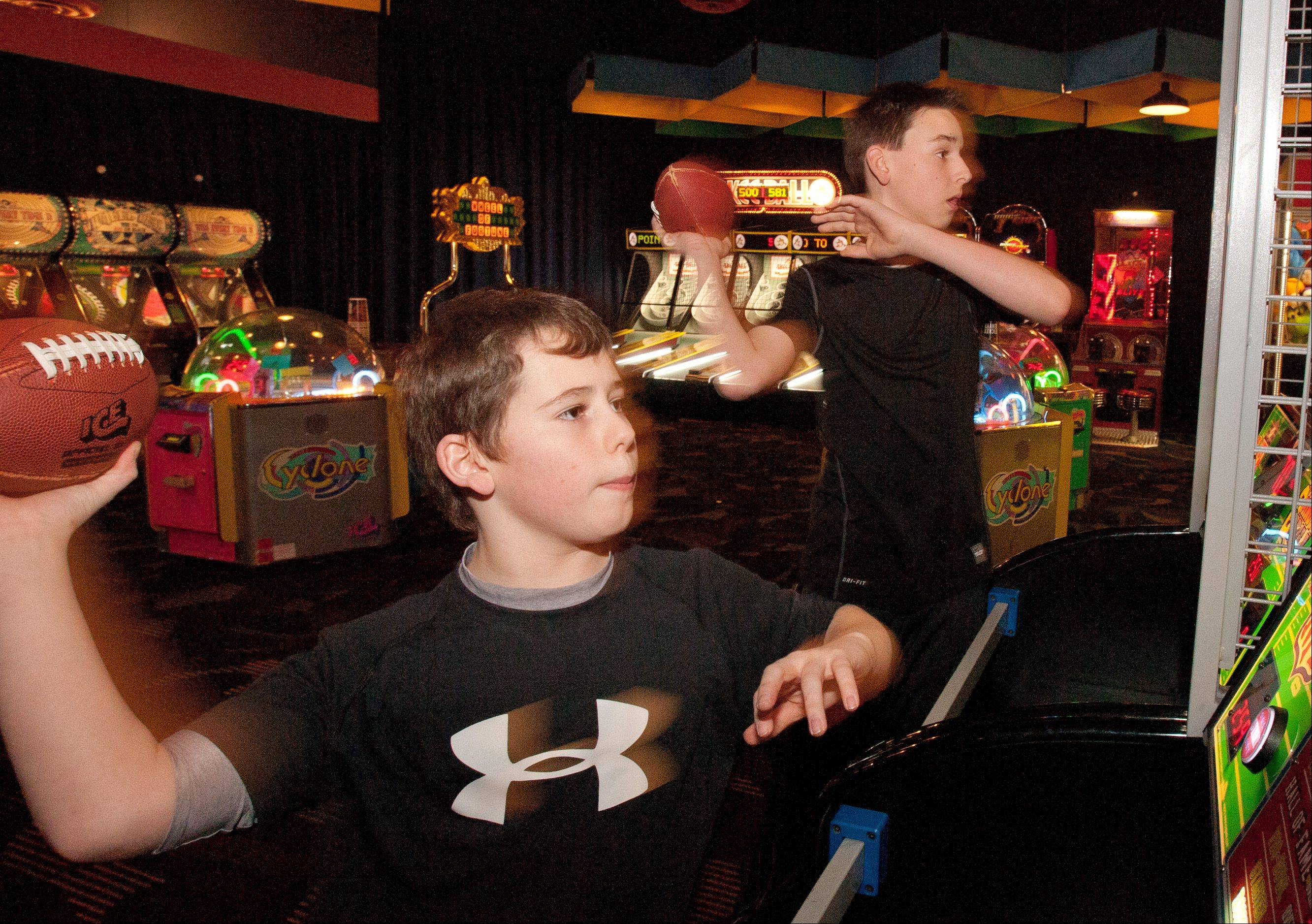 Griffin Coleman, 12, of Plainfield, left, and Andrew Gorski, 12, of Plainfield, right, play interactive video games at Dave and Buster's in Addison.
