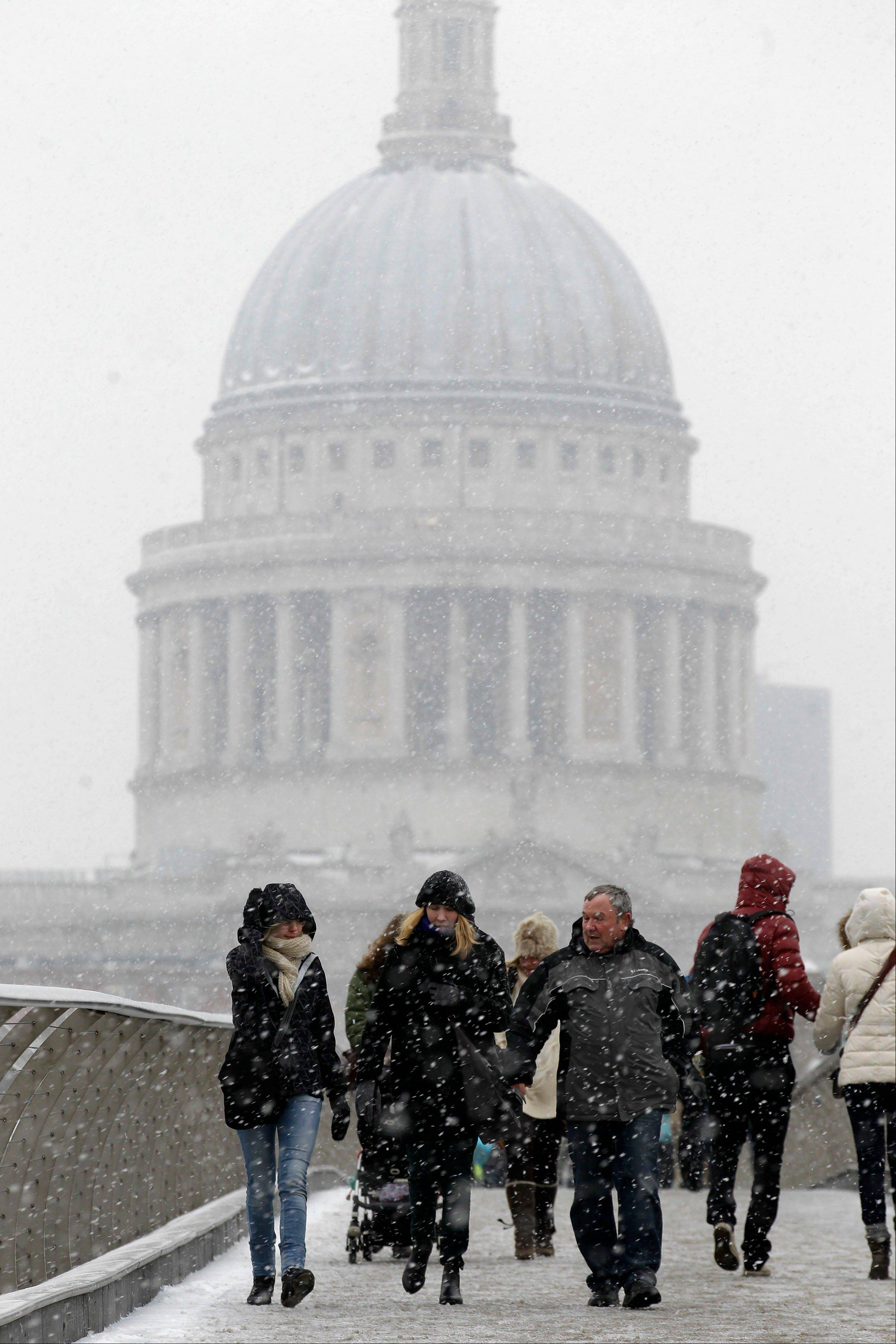 People walk across a snowy Millennium Bridge near St. Paul's Cathedral in London.