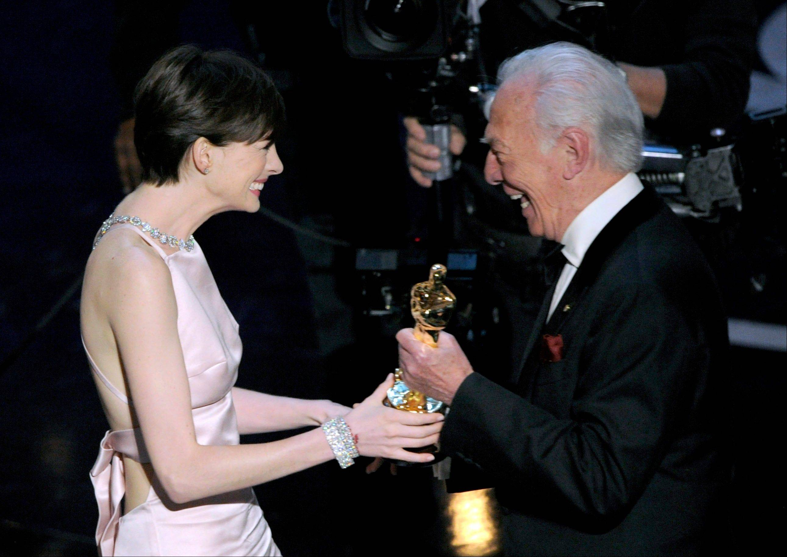 "Christopher Plummer, who won best supporting actor last year for ""Beginners,"" right, presents the award for best actress in a supporting role to Anne Hathaway for ""Les Miserables"" during Sunday's Oscars."