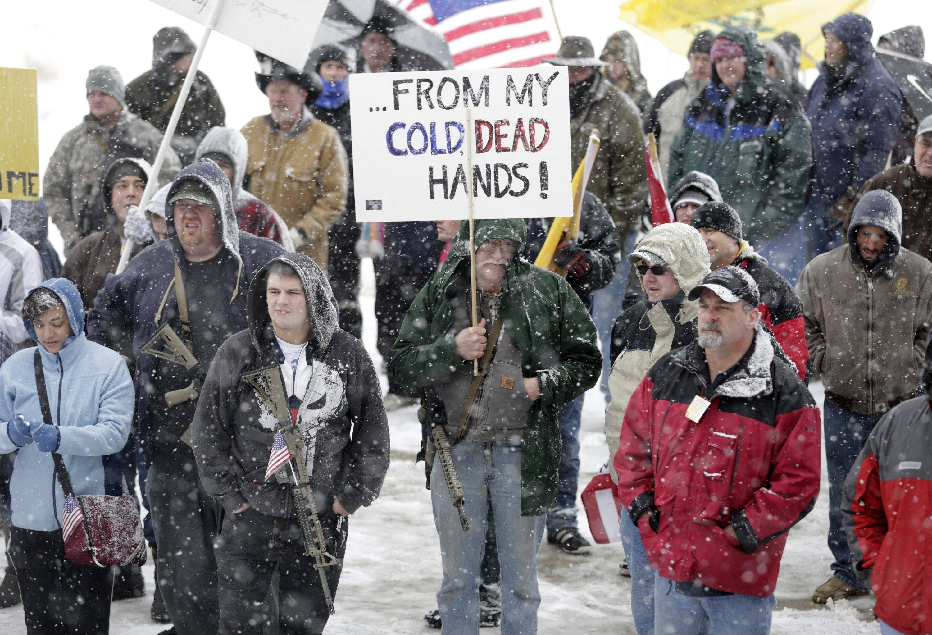 "Gun-rights activist Dave Larson, of Bountiful, Utah, carries his AR-15 rifle and a sign which reads, ""...From my cold, dead hands"" during a ""National Day of Resistance"" rally at the Utah State Capitol in Salt Lake City, Utah, Saturday. Activists said they were were there to show their support for the U.S. Constitution and the 2nd Amendment."