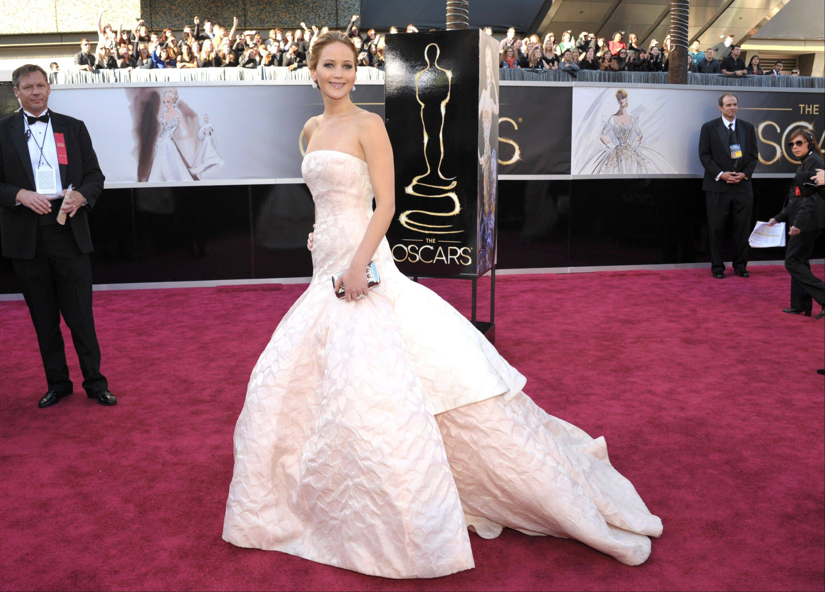 Oscar nominee Jennifer Lawrence changes up her look a bit with this pale pink gown from Dior Haute Couture.