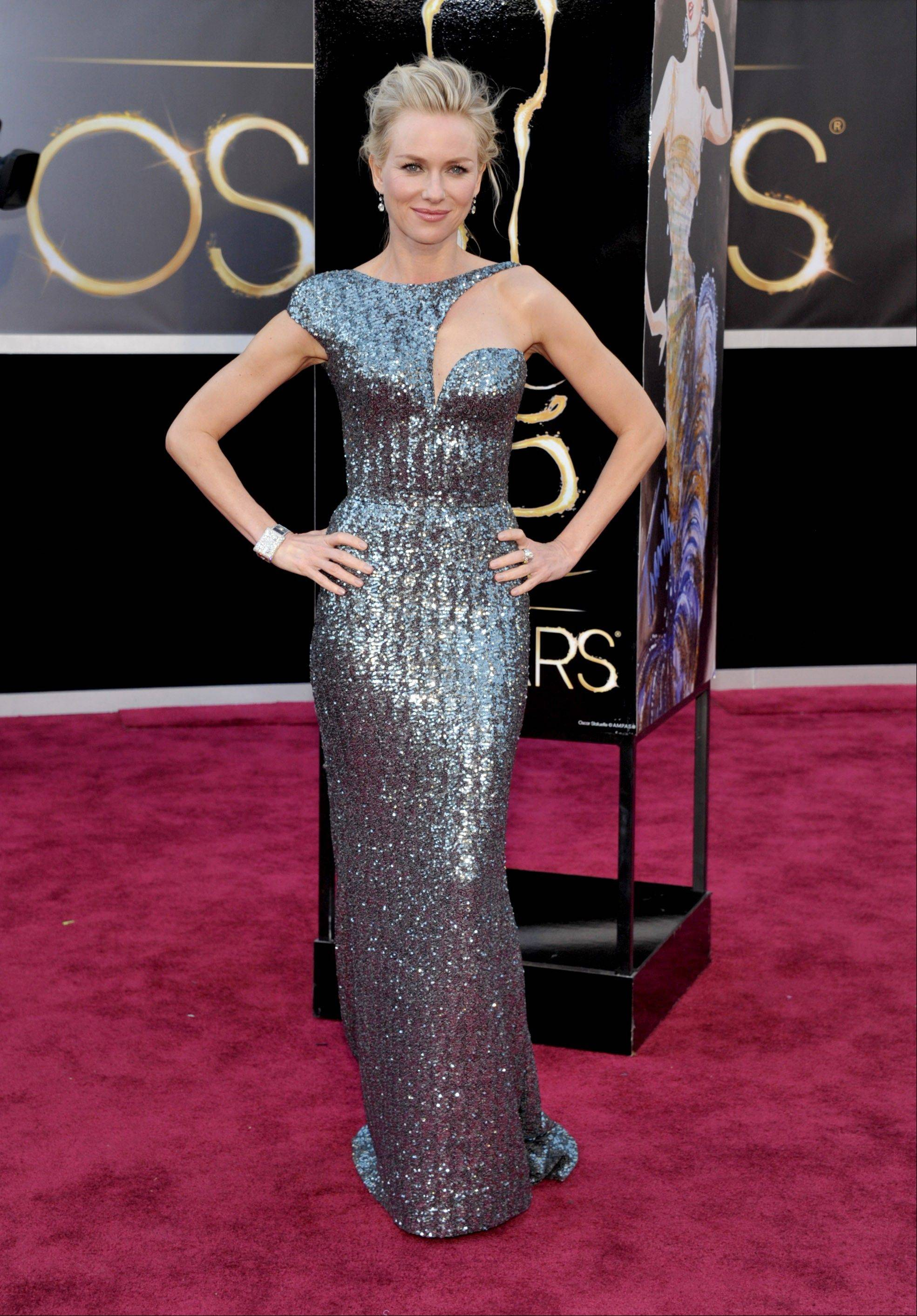 Oscar nominee Naomi Watts opts for not gold but a more metallic gown with a cut out along the neckline from Armani.