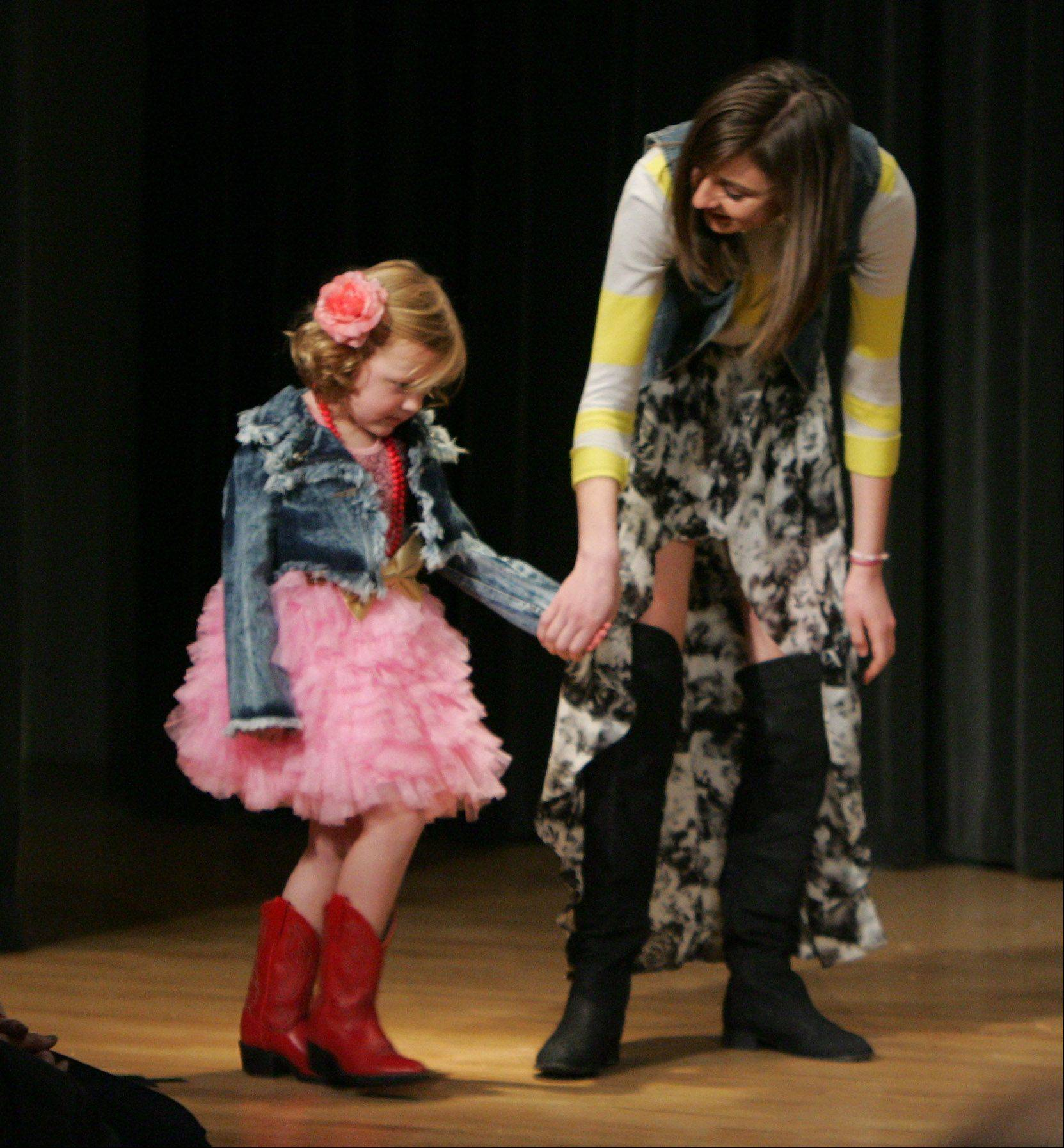"Designer Maddy Gustafson helps the shy Phoebe Welsh walk down the runway Sunday during the first student-run charity fashion show, ""Hope's In Style,"" at the Garland's Center for the Performing Arts in Barrington. The fashion show raised funds for a Guatemalan family living in a garbage dump in Guatemala City."
