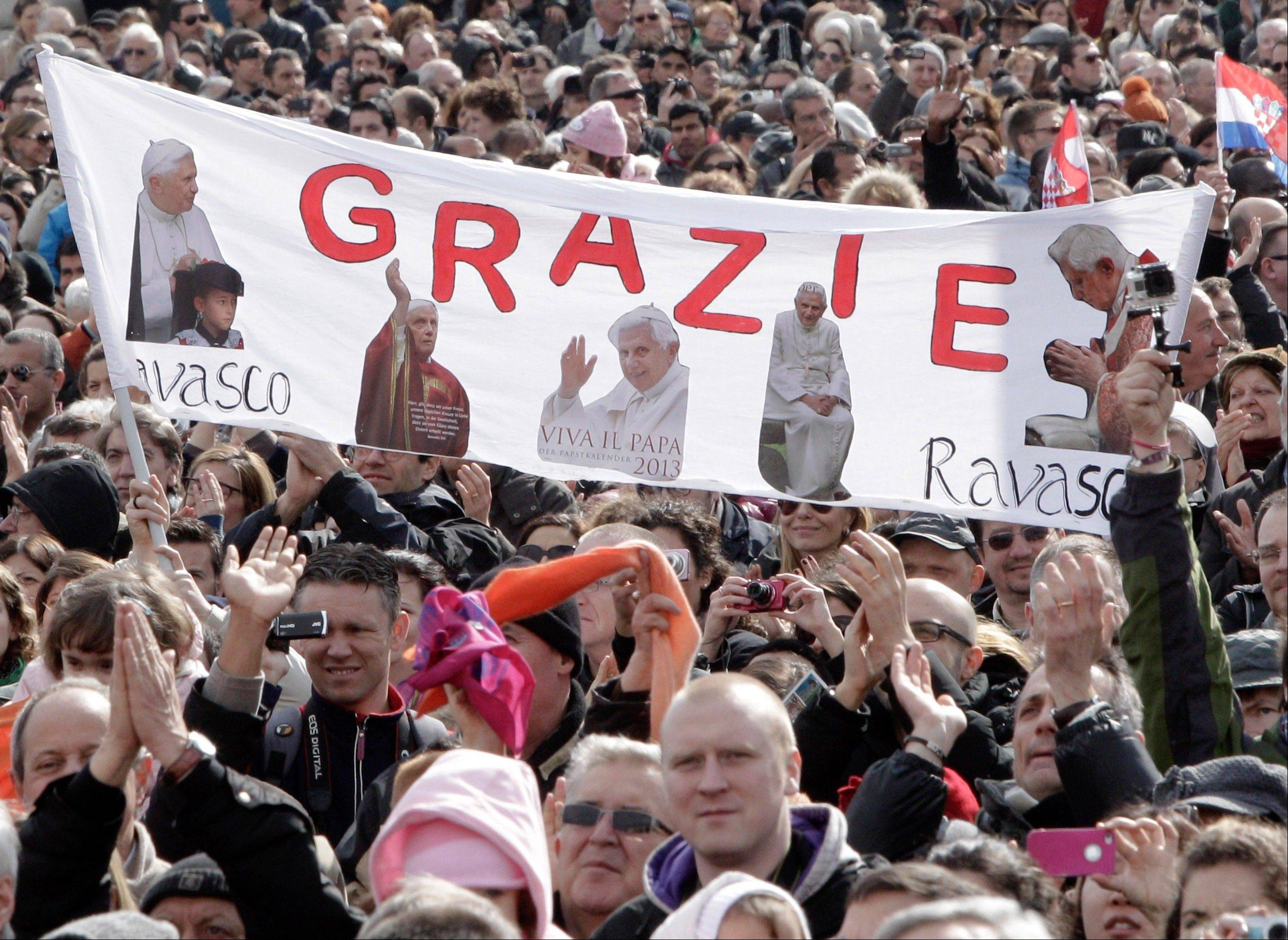 "Faithful hold up a banner with pictures of Pope Benedict XVI and writing reading in Italian ""Thank you"" as they attend Benedict's last Angelus prayer, in St. Peter's Square, at the Vatican, Sunday."