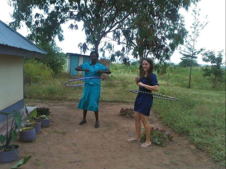 "As co-founder and CEO of MPrep, an innovative educational venture sweeping across Kenya, Bartlett native Toni Maraviglia, right, finds time for a little hula hoop fun with her ""Mama Eunice"" outside Maraviglia's hut."