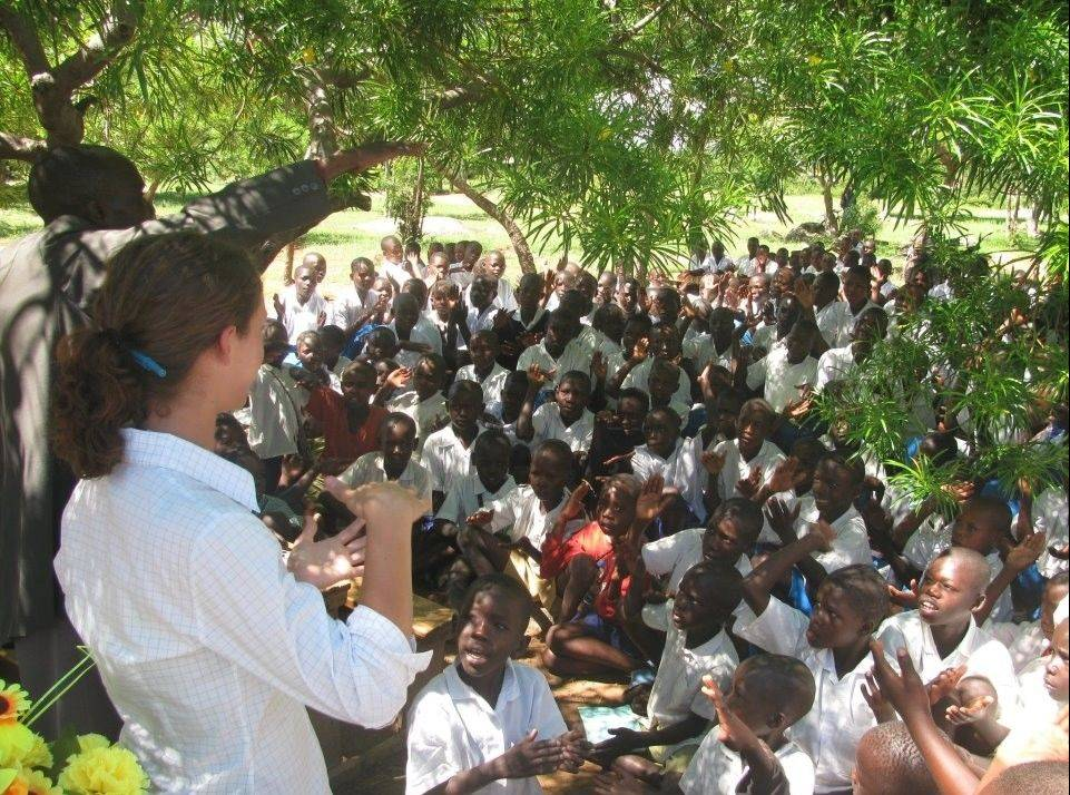 With her innovative educational program that uses cellphones to help teach, Bartlett native Toni Maraviglia, the woman in the white blouse, earns applause from these students in the fishing village of Muhuru Bay, Kenya.
