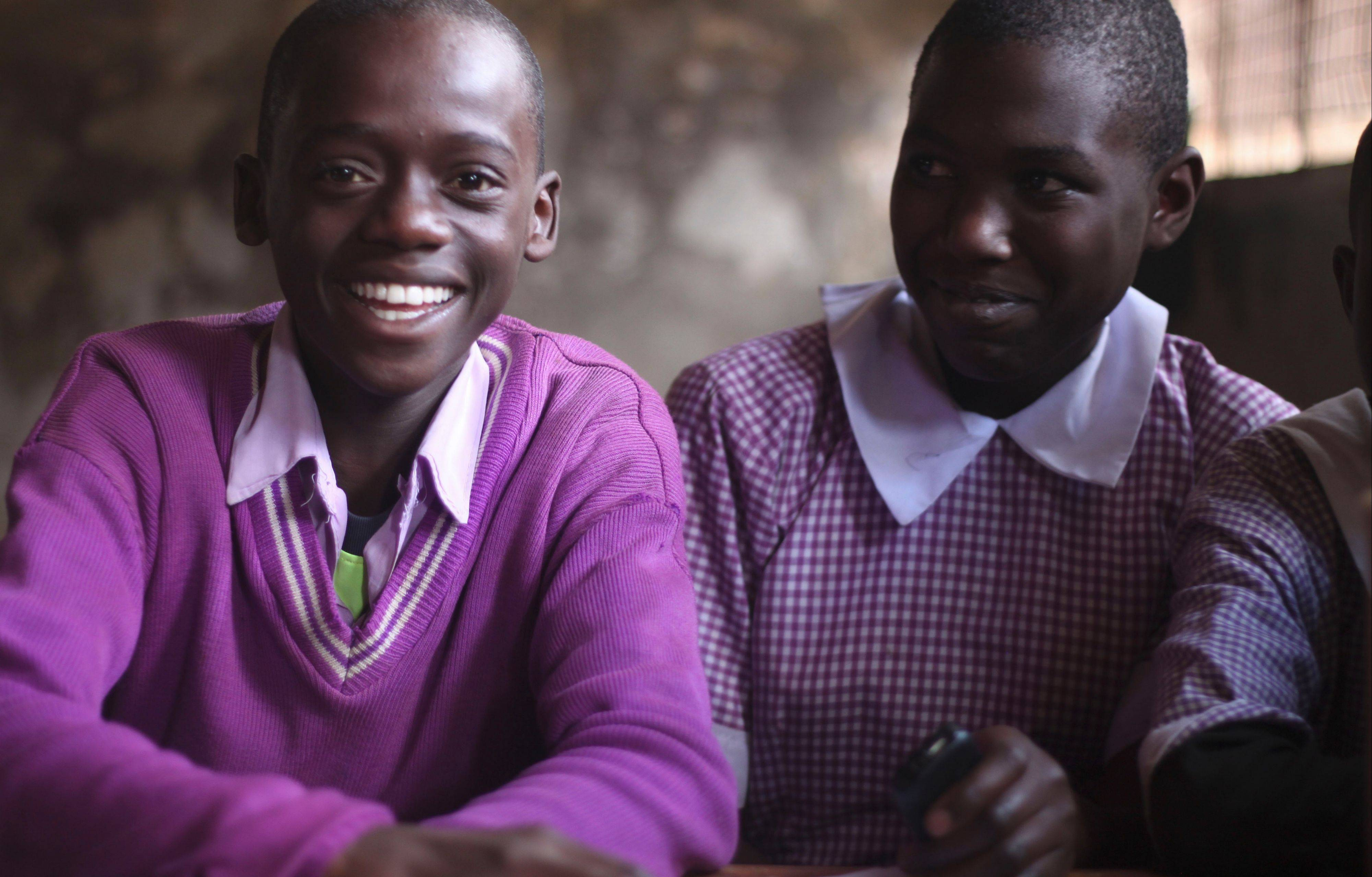 Boys Maxwel, left, and Lavender use cellphones at Chandaria Primary School in Nairobi, Kenya, thanks to an innovative educational program started by Bartlett native Toni Maraviglia.