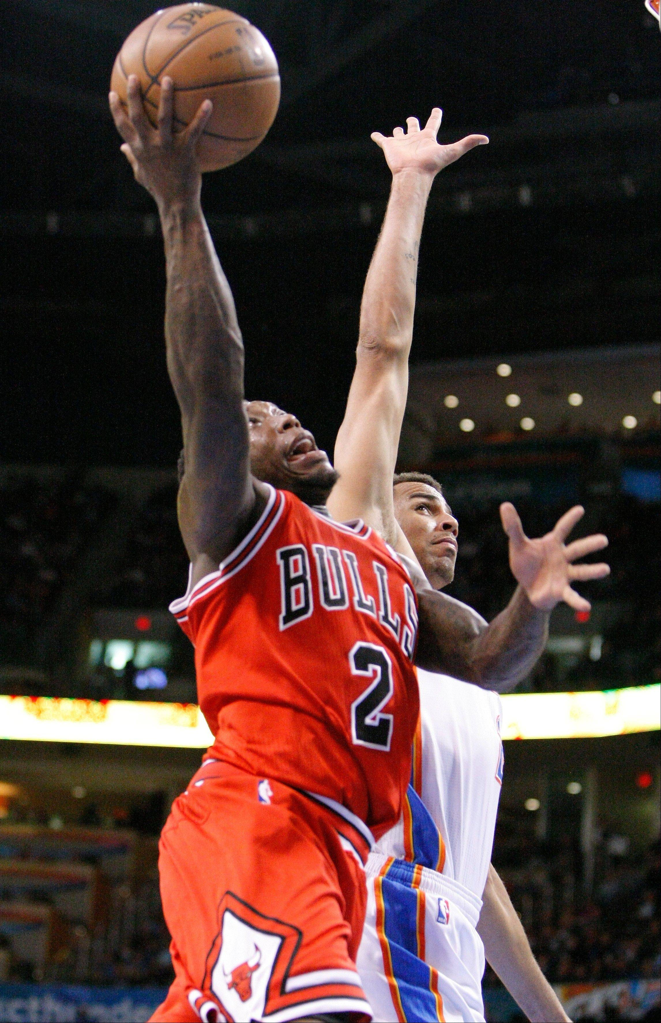 Chicago Bulls guard Nate Robinson, front, goes to the basket next to Oklahoma City Thunder guard Thabo Sefolosha during the second quarter of an NBA basketball game in Oklahoma City, Sunday, Feb. 24, 2013.