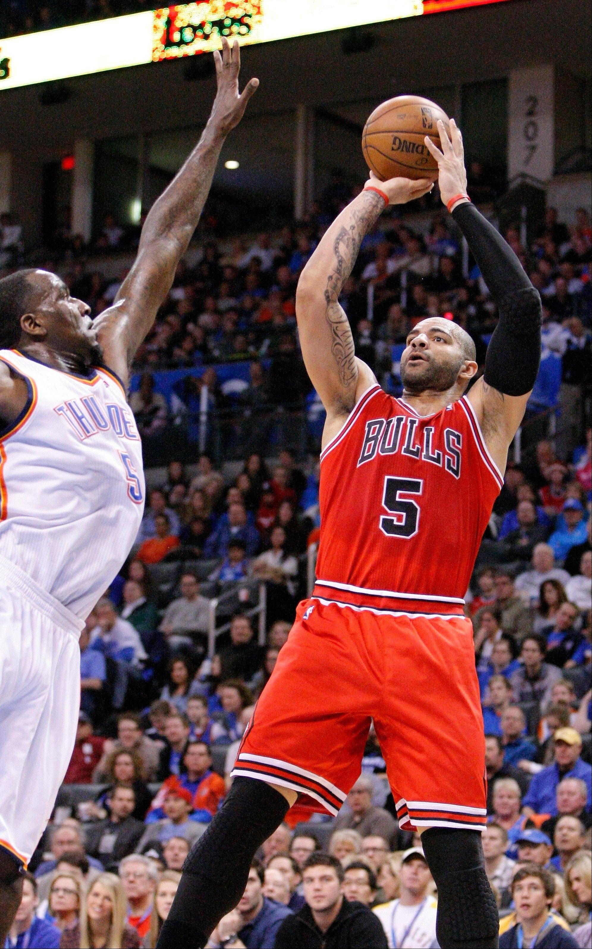 Chicago Bulls forward Carlos Boozer goes up for a basket as Oklahoma City Thunder center Kendrick Perkins defends during the first quarter of an NBA basketball game in Oklahoma City, Sunday, Feb. 24, 2013.