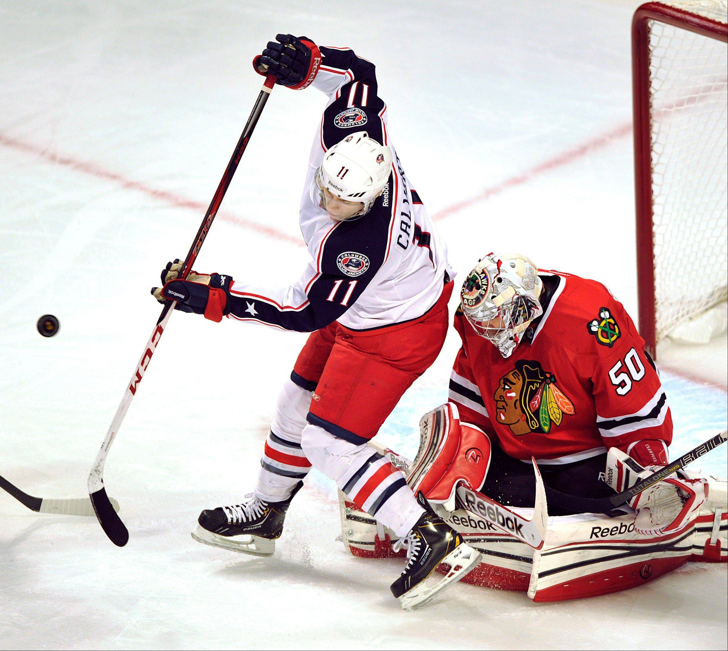Columbus Blue Jackets' Matt Calvert (11) tries to tip the puck past Chicago Blackhawks goalie Corey Crawford (50) during the first period of an NHL hockey game Sunday, Feb. 24, 2013, in Chicago.