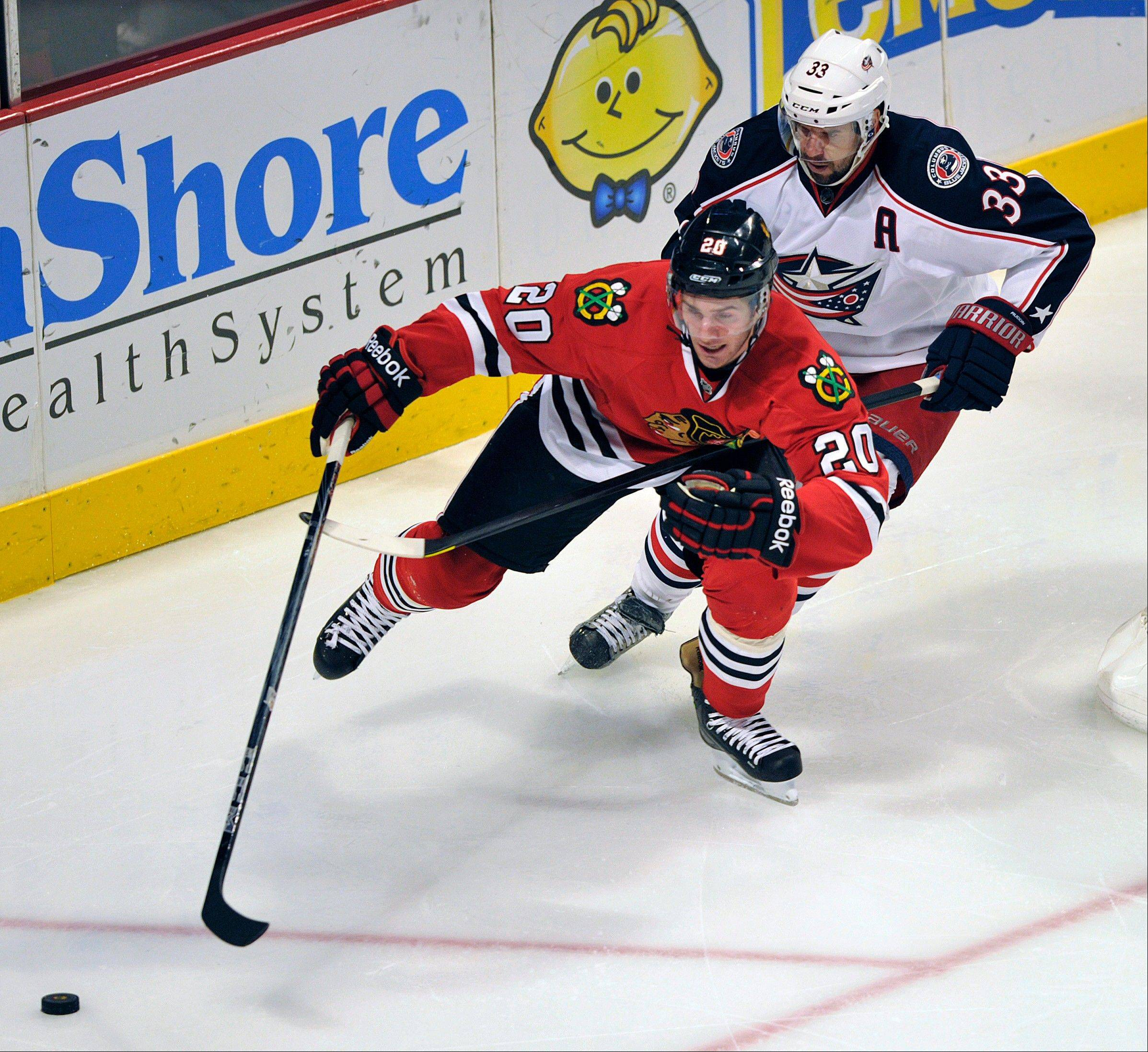 Blackhawks winger Brandon Saad skates towards the puck as Columbus Blue Jackets' Adrian Aucoin defends during the third period of an NHL hockey game Sunday, Feb. 24, 2013, in Chicago. Chicago won 1-0.