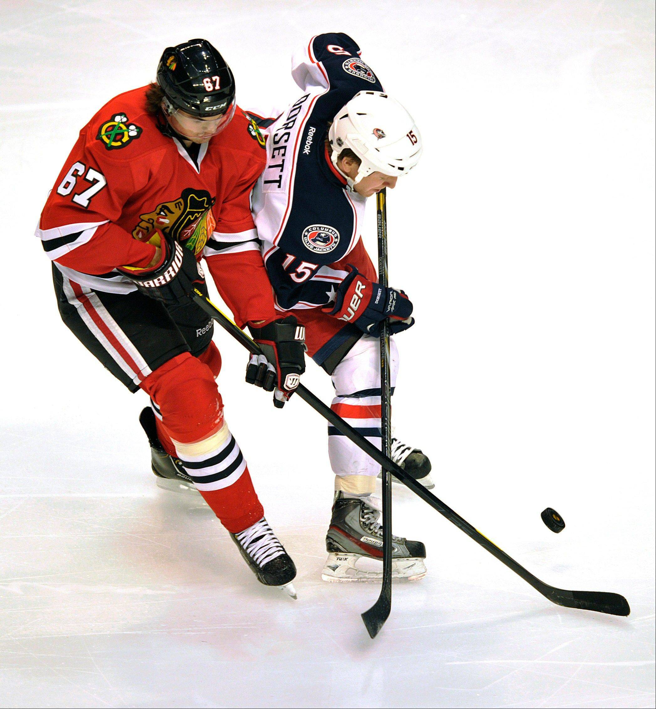 Chicago Blackhawks' Michael Frolik (67) and Columbus Blue Jackets' Derek Dorsett (15) compete for the puck during the first period of an NHL hockey game Sunday, Feb. 24, 2013, in Chicago.