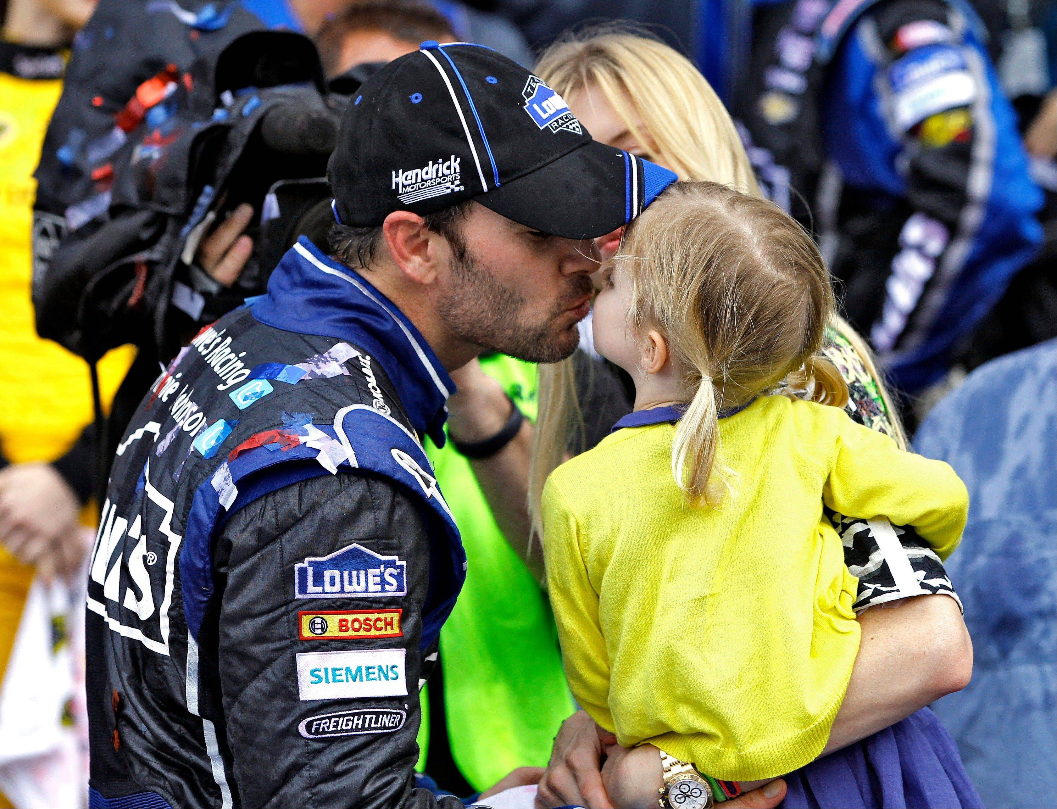 Jimmie Johnson kisses his daughter Genevieve Marie in Victory Lane after winning the Daytona 500 NASCAR Sprint Cup Series auto race, Sunday, Feb. 24, 2013, at Daytona International Speedway in Daytona Beach, Fla.